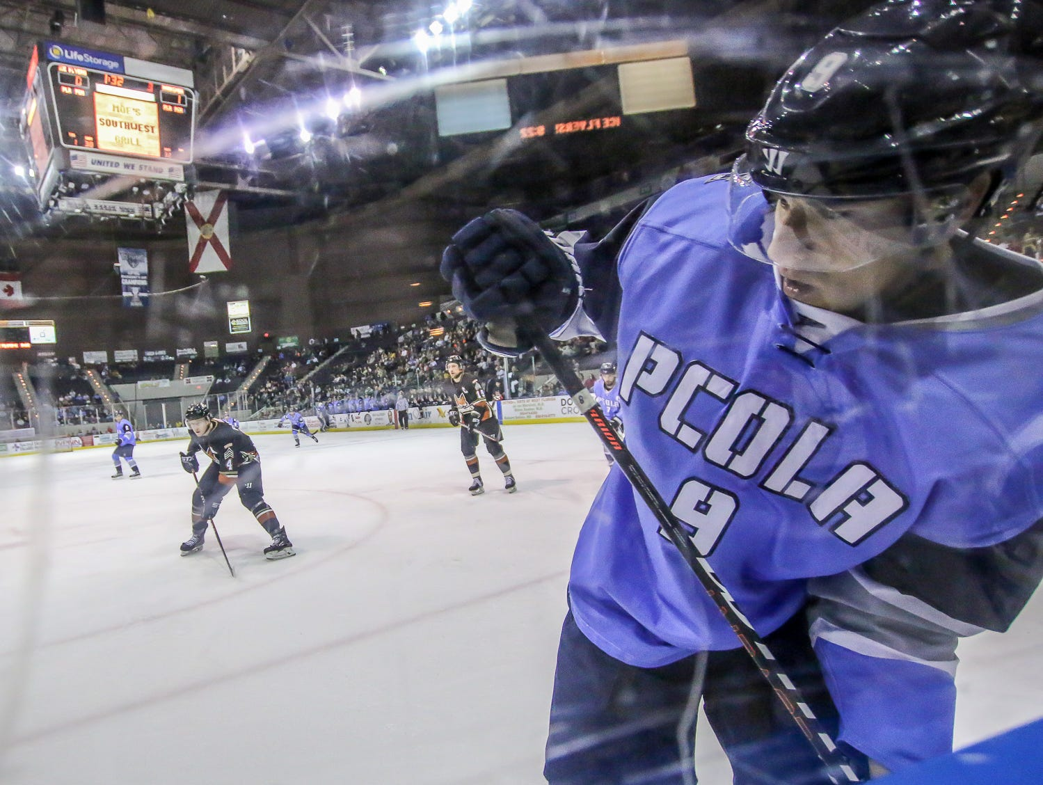 Pensacola's Ryan Marcuz (9) goes up along the glass to clear the puck against Fayetteville at the Pensacola Bay Center on Saturday, January 5, 2019.