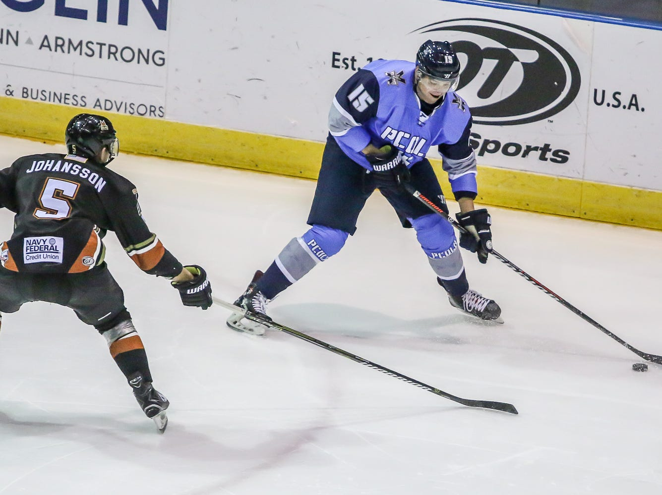 Pensacola's Nathan Bruyere (15) looks to clear the puck past Fayetteville's Alfred Johansson (5) at the Pensacola Bay Center on Saturday, January 5, 2019.
