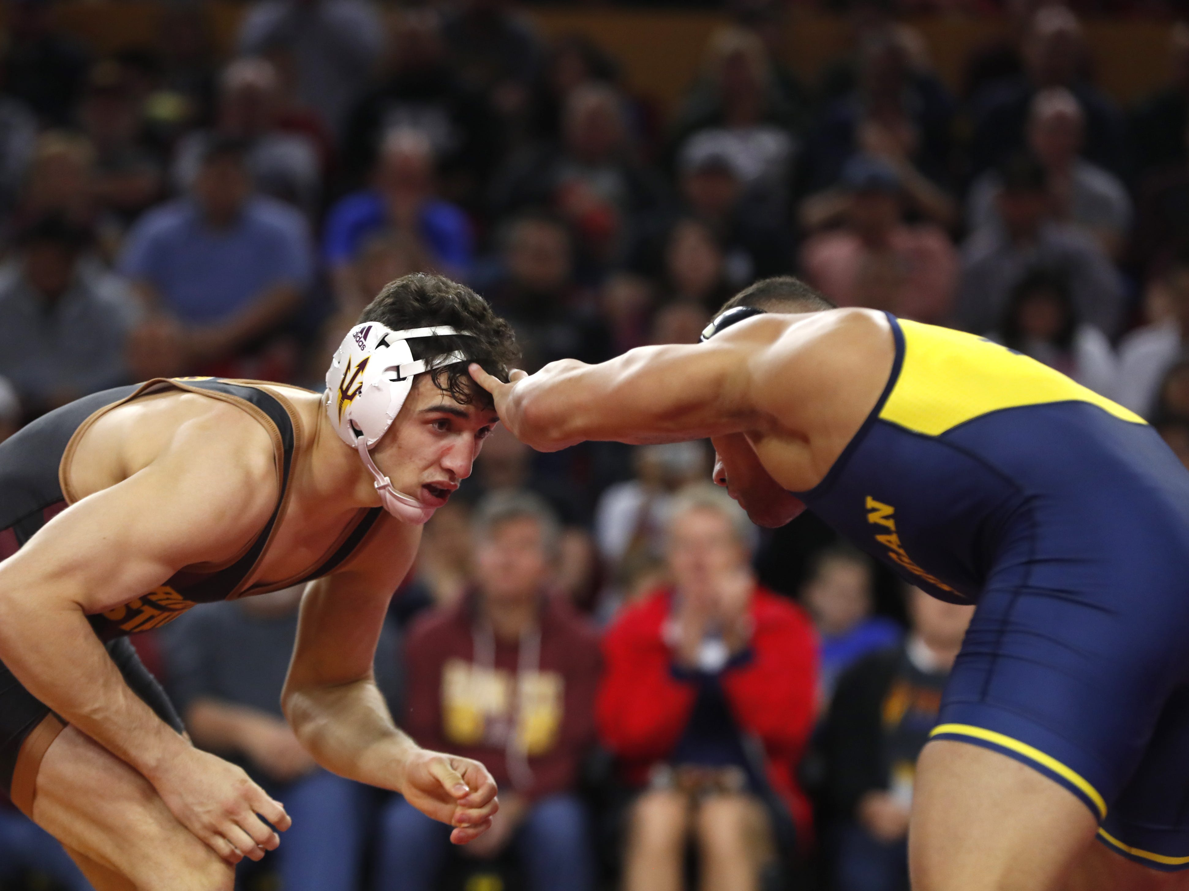 ASU's Christian Pagdilao (in black) wrestles Michigan's Alec Pantaleo (in yellow and blue) during a 157 lbs match at Wells Fargo Arena in Tempe, Ariz. on January 5, 2019.