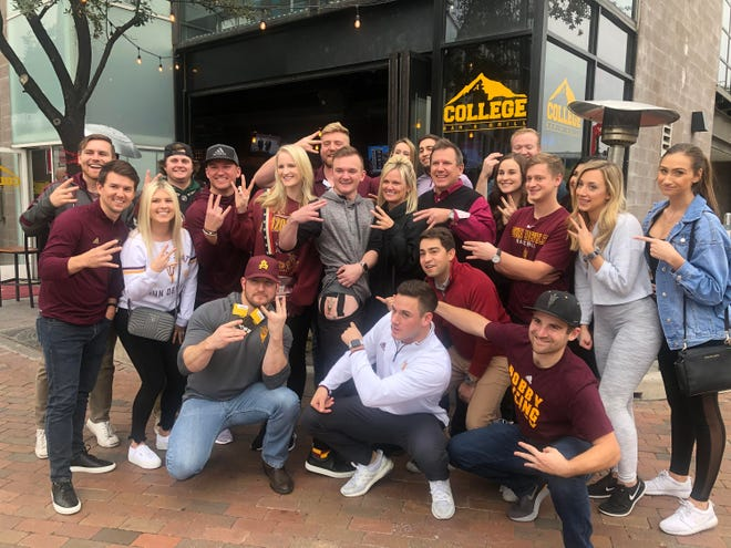 ASU fan Tommy Czerwinski poses with family and friends at College Bar and Grill in Tempe after getting a pitchfork tattoo.