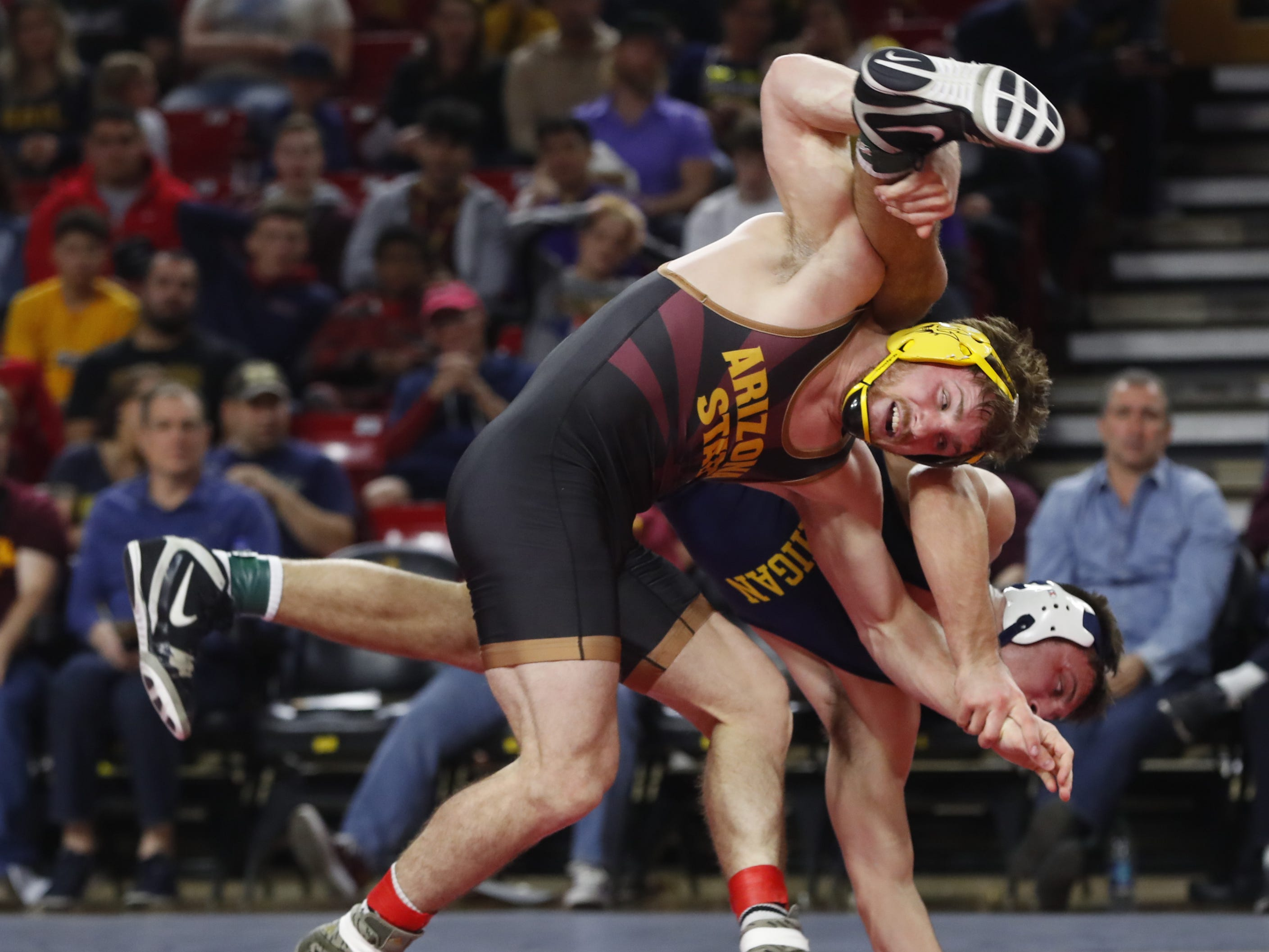 ASU's Jacen Peterson (in black) wrestles Michigan's Reece Hughes during a 184 lbs match at Wells Fargo Arena in Tempe, Ariz. on January 5, 2019.
