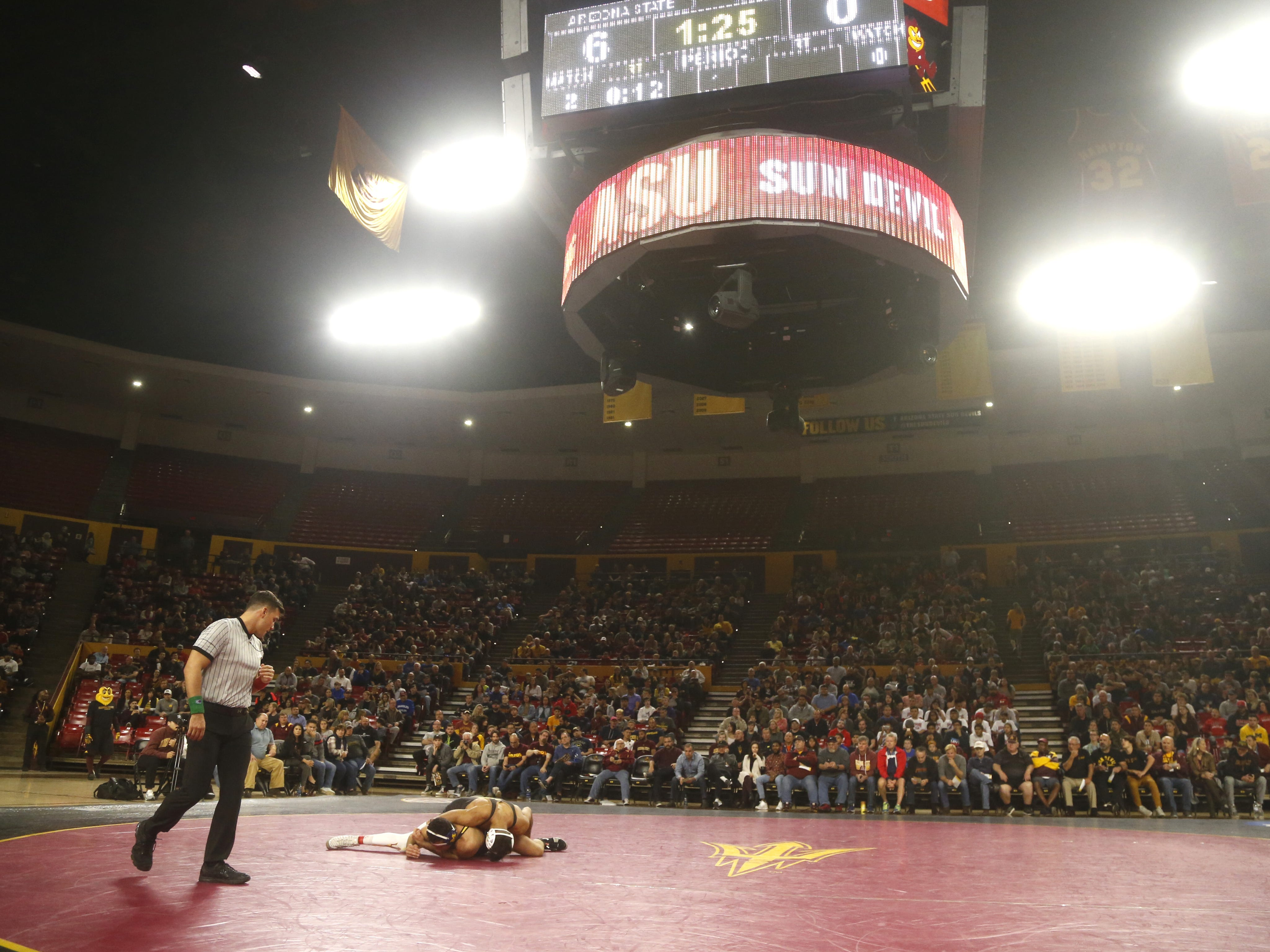 ASU's Josh Shields (in black) wrestles Michigan's Logan Massa (in yellow and blue) during a 165 lbs match at Wells Fargo Arena in Tempe, Ariz. on January 5, 2019.