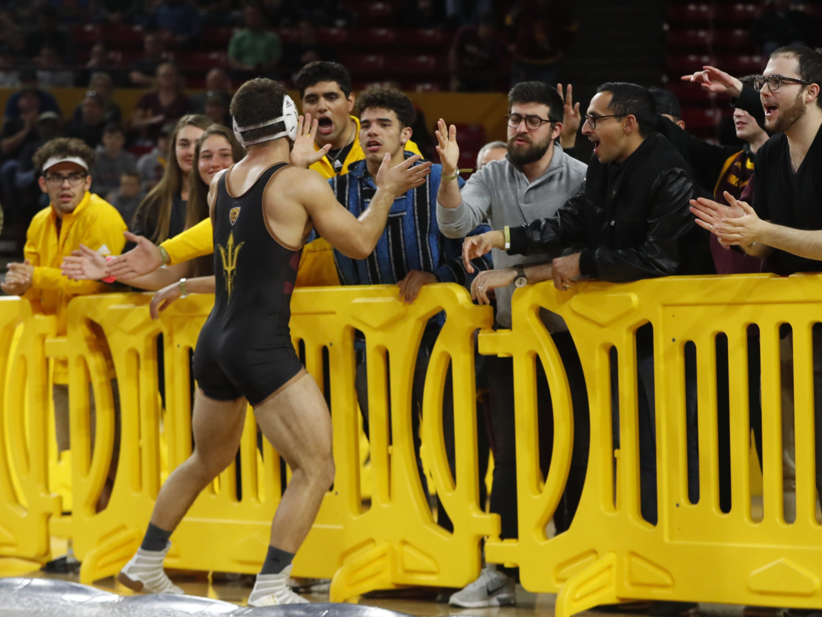 ASU's Josh Shields (in black) celebrates with fans after beating Michigan's Logan Massa (in yellow and blue) during a 165 lbs match at Wells Fargo Arena in Tempe, Ariz. on January 5, 2019.