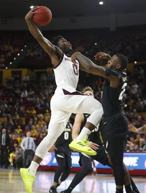 ASU's Luguentz Dort (0) dunks over Colorado's McKinley Wright IV (25) during the first half at Wells Fargo Arena in Tempe, Ariz. on January 5, 2019.