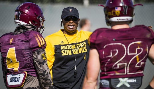 Running backs coach John Simon belts out instructions to Demario Richard, left, and Nick Ralston at Arizona State University football practice, Monday, March 28, 2016.
