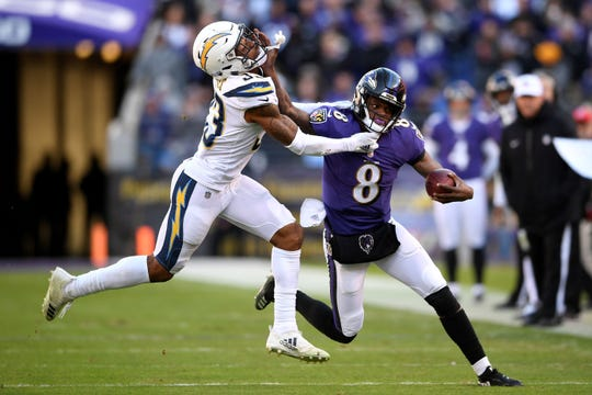 Baltimore Ravens quarterback Lamar Jackson, right, rushes against Los Angeles Chargers free safety Derwin James during an NFL wild-card playoff football game on Sunday, Jan. 6, in Baltimore. (AP Photo/Nick Wass)