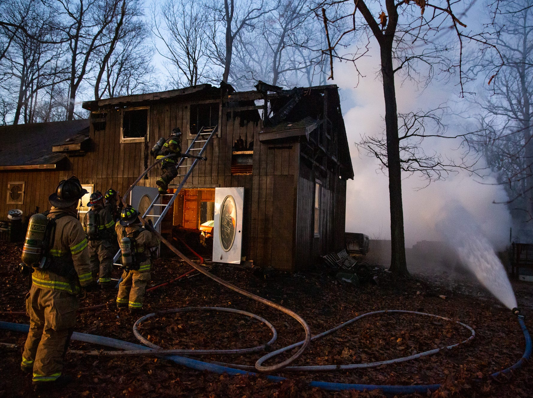 Firefighters work in front of a large detached garage at the scene of a well-involved working house fire on the 200 block of Waldheim Rd., early Sunday, Jan. 6, 2019, in Hamilton Township. Hampton Fire Chief P.J. Trimmer said that the sole occupant of the house was able to escape safely with his dog, and there were no injuries in the fire. The house, which collapsed into the basement, is a total loss, and the detached garage suffered extensive damage, said Trimmer.