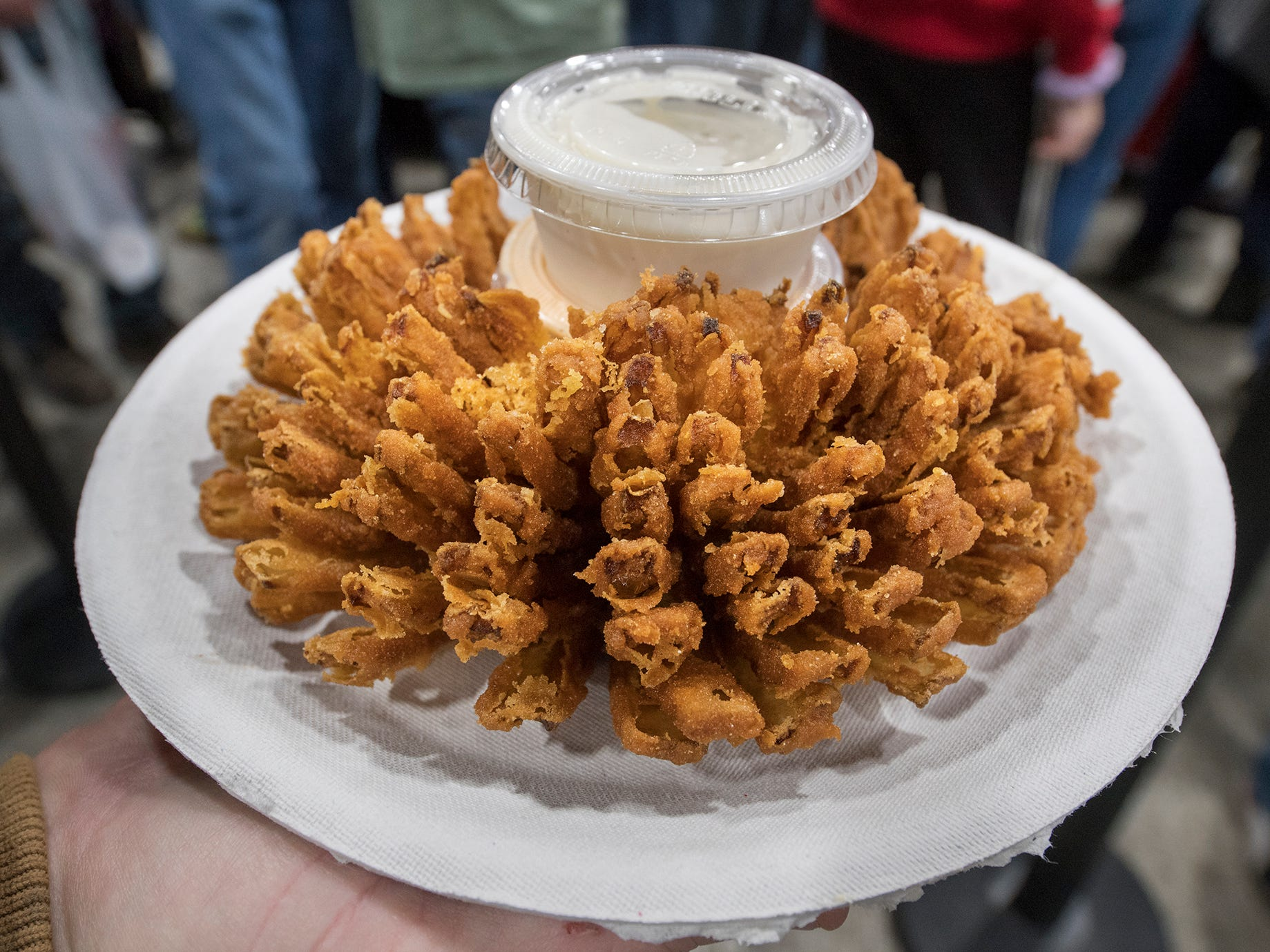 A blooming onion is carried back to a table to be eaten during The 103rd Pennsylvania Farm Show in Harrisburg Sunday January 6, 2019.