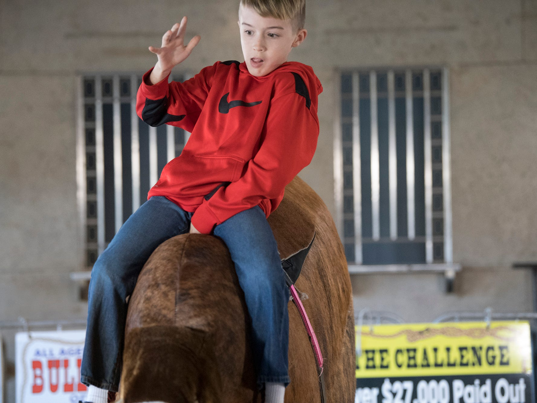 Gage Feldman, age 10 of Chambersburg, rides a mechanical bull during The 103rd Pennsylvania Farm Show in Harrisburg Sunday January 6, 2019.