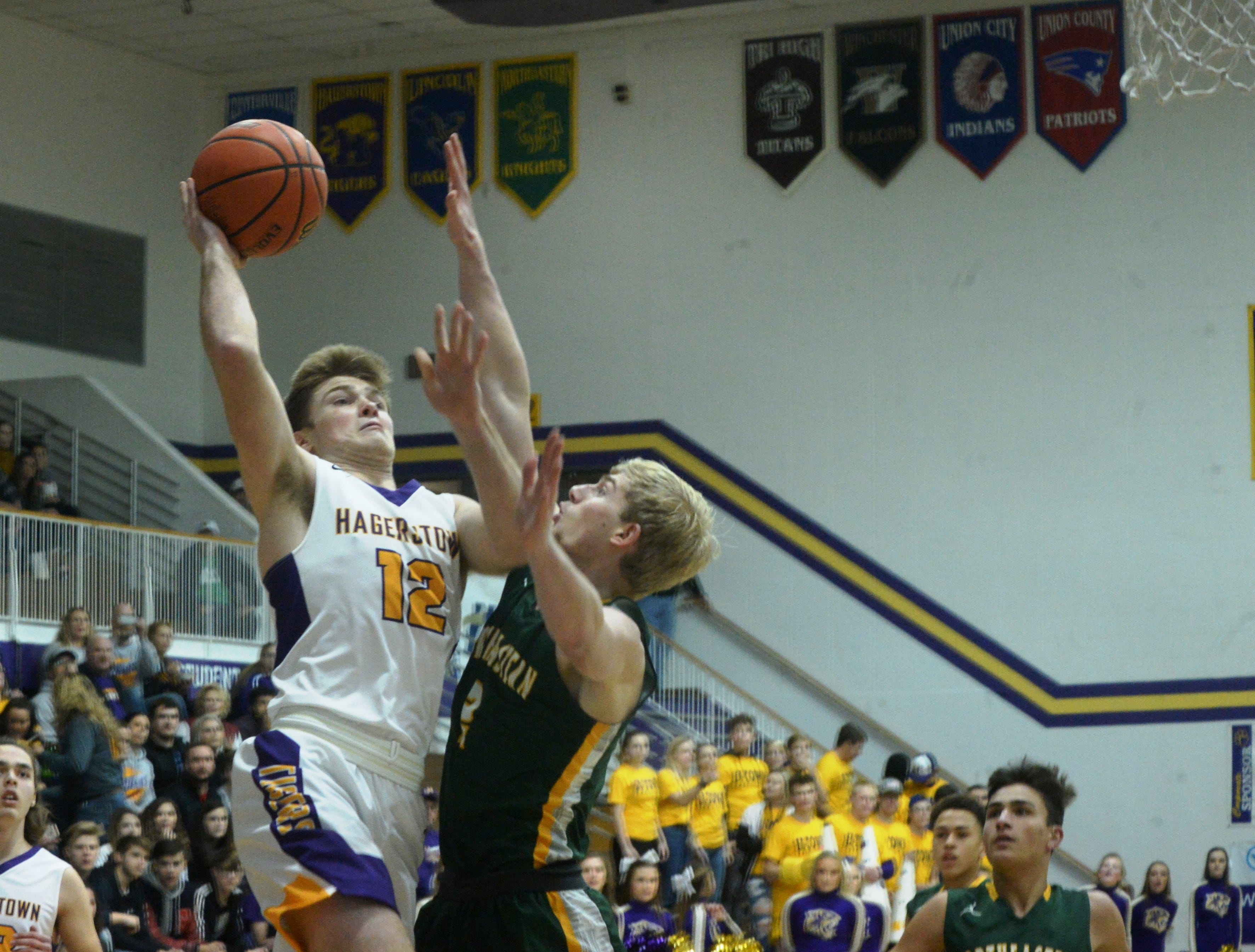 Hagerstown's Cody Swimm (12) shoots over Northeastern's Carter Lumpkin during the Wayne County boys basketball championship at Hagerstown Saturday, Jan. 5, 2019. Hagerstown defeated Northeastern 37-35 to win the girls' title, and Northeastern beat Hagerstown 60-49 in the boys championship.