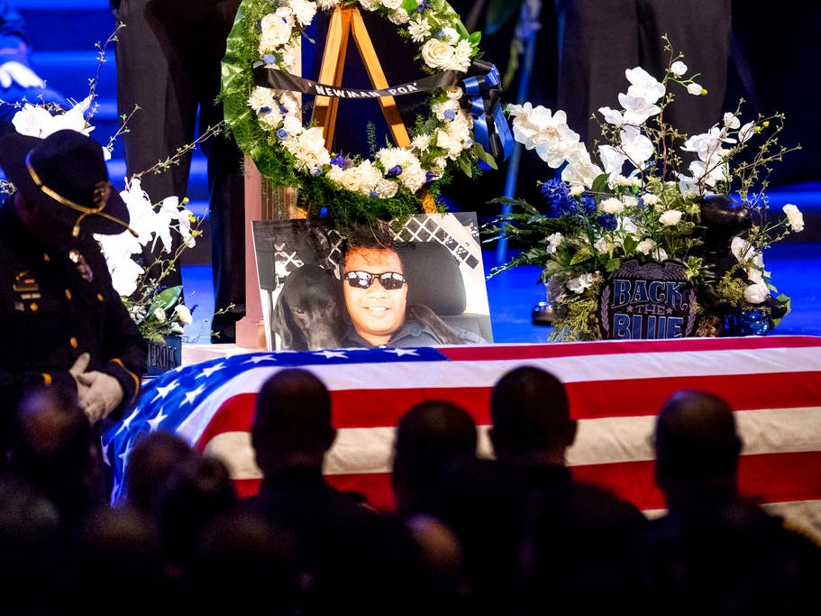 "A picture of slain Newman police Cpl. Ronil ""Ron"" Singh rests atop the casket during his funeral on Saturday, Jan. 5, 2019, in Modesto, Calif. According to authorities, prosecutors have charged Gustavo Perez Arriaga, who was in the United States illegally, with Singh's killing."