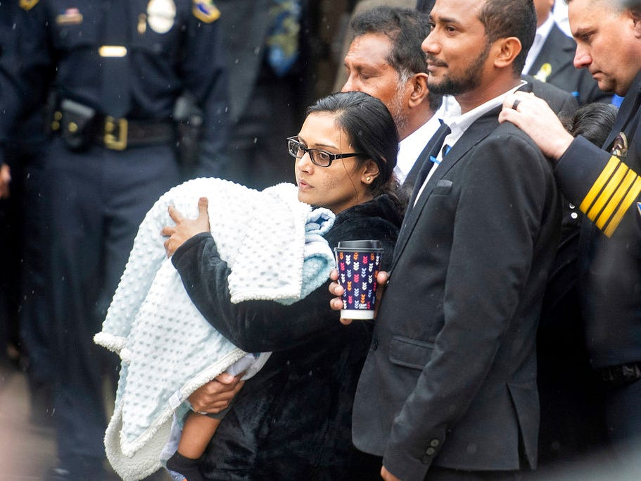 "Anamika Singh, widow of slain Newman Police Cpl. Ronil ""Ron"" Singh, holds their 5-month-old child during her husband's funeral on Saturday, Jan. 5, 2019, in Modesto, Calif. According to authorities, prosecutors have charged Gustavo Perez Arriaga, who was in the United States illegally, with Singh's killing."
