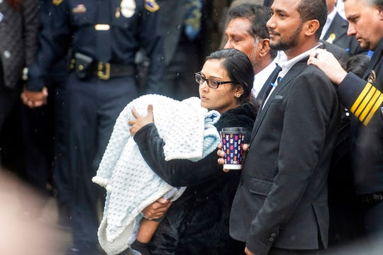 """Anamika Singh, widow of slain Newman Police Cpl. Ronil """"Ron"""" Singh, holds their 5-month-old child during her husband's funeral on Saturday, Jan. 5, 2019, in Modesto, Calif. According to authorities, prosecutors have charged Gustavo Perez Arriaga, who was in the United States illegally, with Singh's killing."""