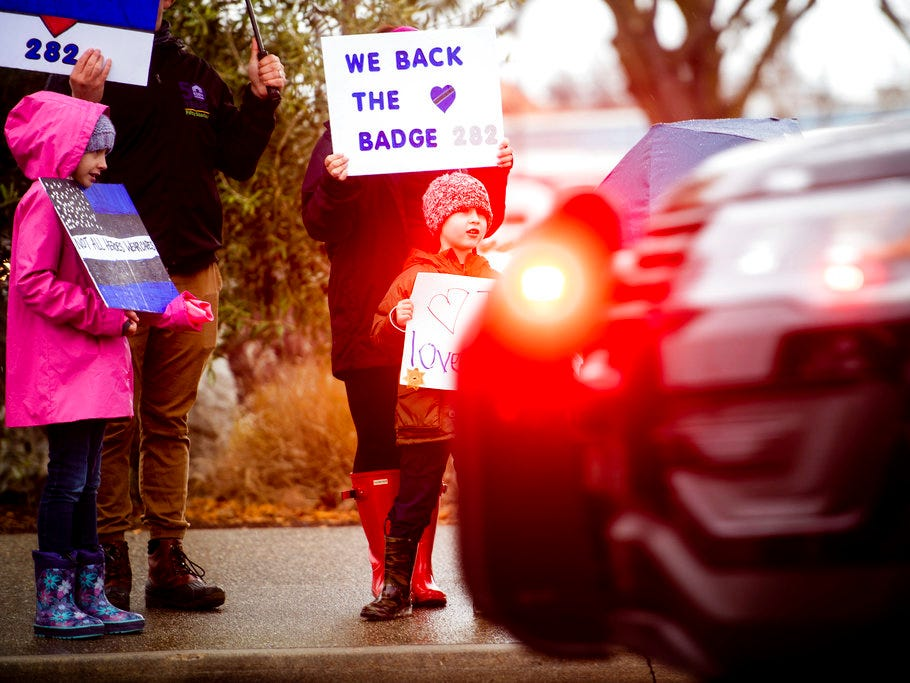 "Rhett Heron, 5, holds a sign as a procession accompanies the body of slain Newman police Cpl. Ronil ""Ron"" Singh on Saturday, Jan. 5, 2019, in Modesto, Calif. According to authorities, prosecutors have charged Gustavo Perez Arriaga, who was in the United States illegally, with Singh's killing."