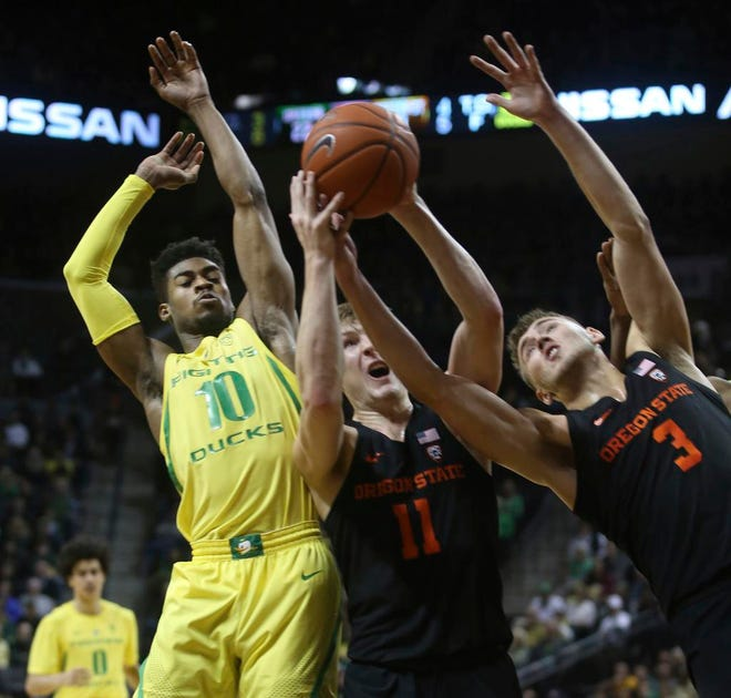 Oregon's Victor Bailey Jr., left, goes up for a rebound against Oregon State's Zach Reichle and Tres Tinkle during the first half of an NCAA college basketball game Saturday, Jan. 5, 2019, in Eugene, Ore. (AP photo/Chris Pietsch)