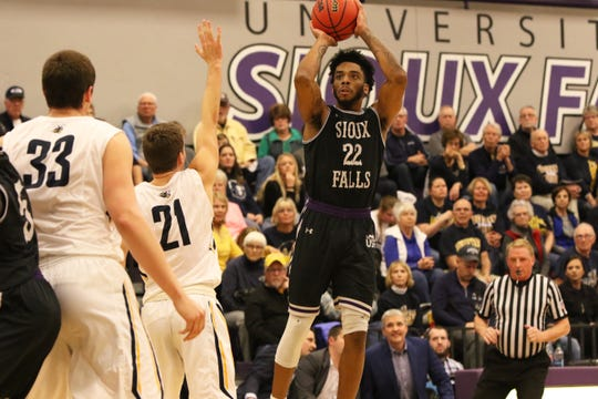 Justin Taylor of USF gets off a shot past A.J. Plitzuweit of Augustana during Saturday night's game at USF.