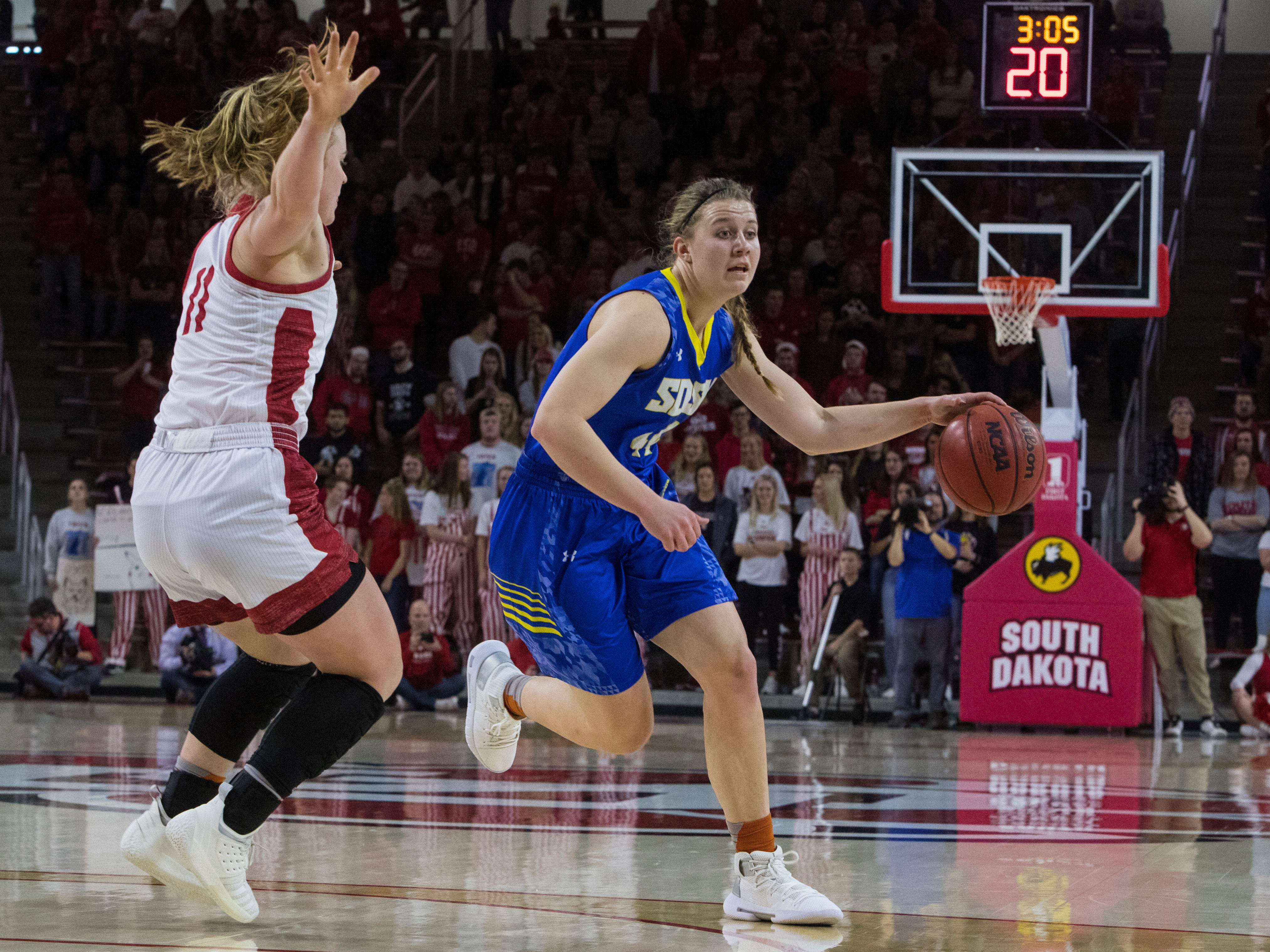 SDSU's Myah Selland (44) dribbles the ball past USD's Monica  Arens (11) during a game, Sunday, Jan. 6, 2019 in Vermillion, S.D.