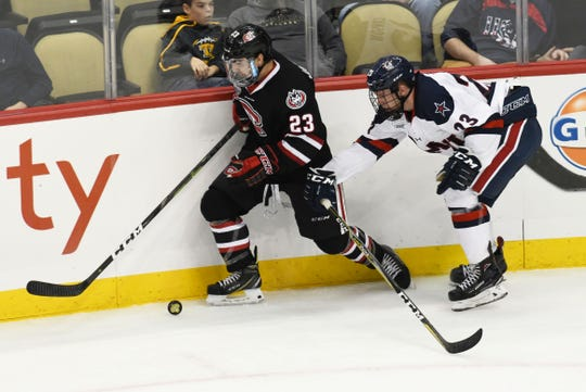 St. Cloud State's Robby Jackson (left) fights for the puck along the boards with Robert Morris' Geoff Lawson. Jackson had two goals in SCSU's 5-2 win Saturday in Pittsburgh.