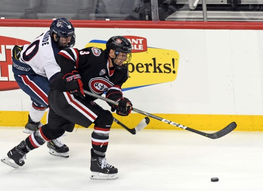 St. Cloud State's Jack Poehling advances the puck with Robert Morris' Nick Lalonde in pursuit. The Huskies beat the Colonials, 5-2 Saturday in Pittsburgh.