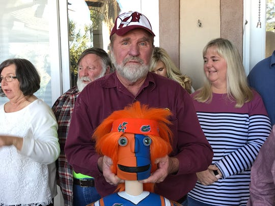 FSU fan Olin Granthum holds a trophy decorated in Florida colors.