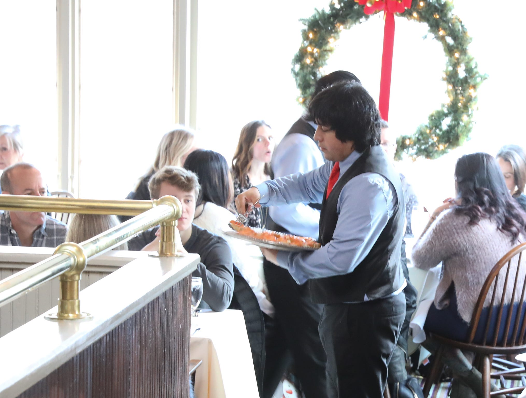 Servers deliver brunch menu items to the tables during Sunday brunch at Restaurant X in Congers on Sunday, January 6, 2019.