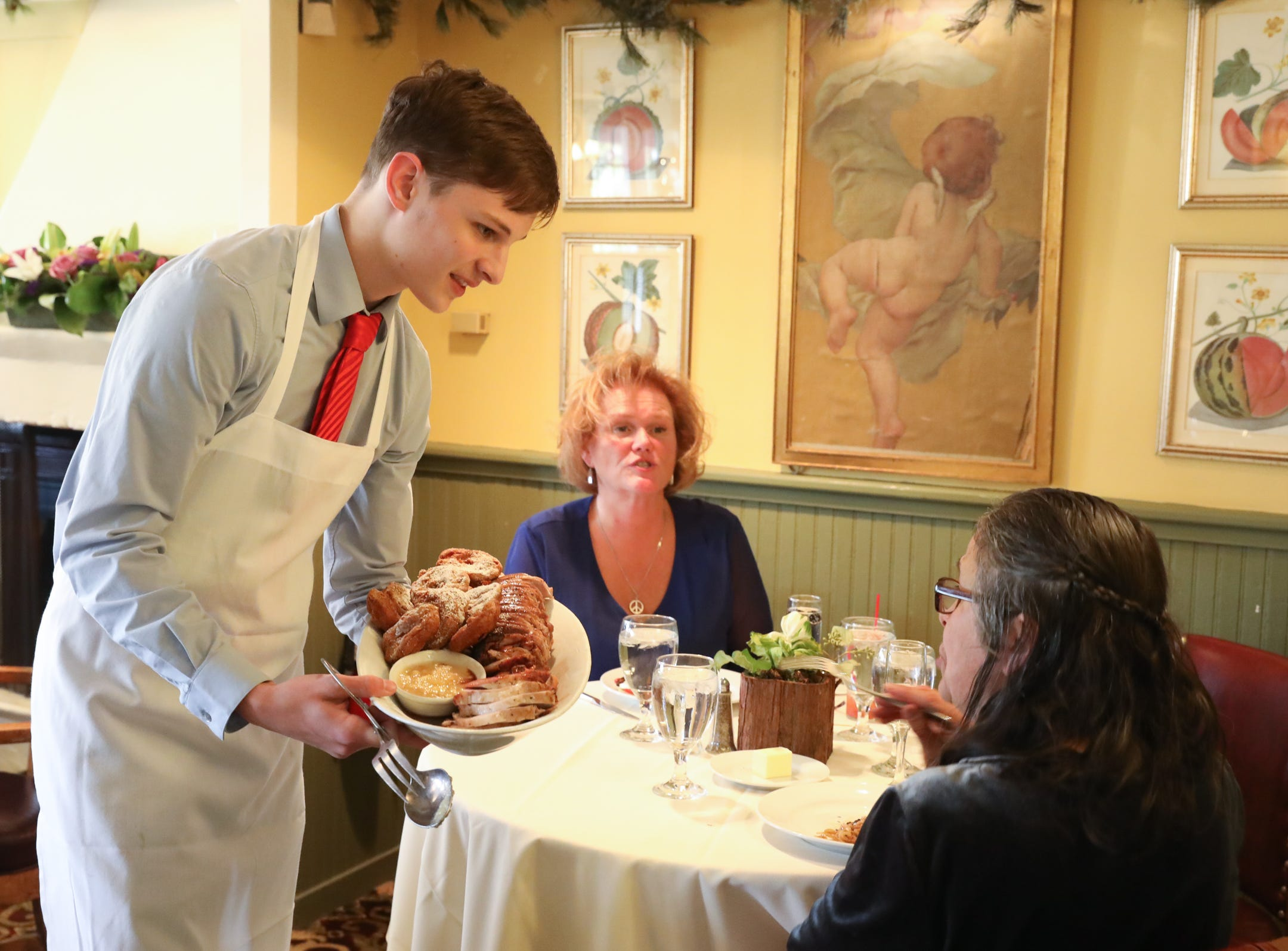 A server serves Roast Pork Tenderlion with Apple Sauce table side during Sunday brunch at Restaurant X in Congers on Sunday, January 6, 2019.
