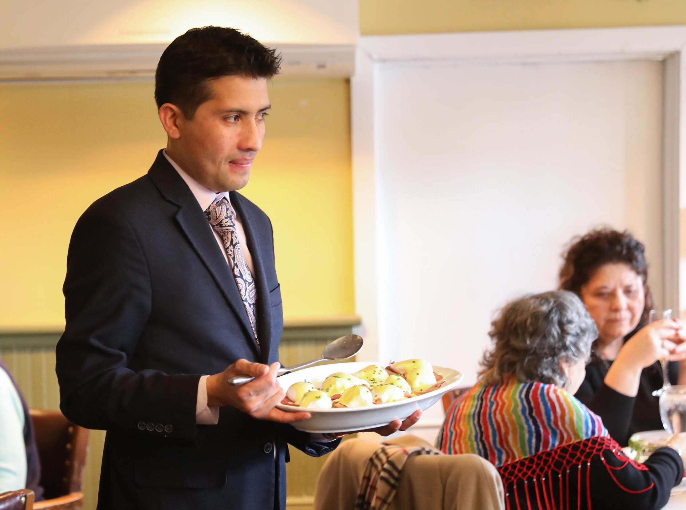 A Maitre D serves Eggs Benedict during Sunday brunch at Restaurant X in Congers on Sunday, January 6, 2019.