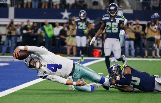 Dallas Cowboys quarterback Dak Prescott (4) advances the ball to the 1-yard line on a short run for the end zone as Seattle Seahawks safety Bradley McDougald (30) makes the stop during the second half of the NFC wild-card NFL football game in Arlington, Texas, Saturday, Jan. 5, 2019.