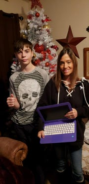 Tammy Byars and her son, Brady, display a computer repaired and donated to them by Daniel Hernandez.