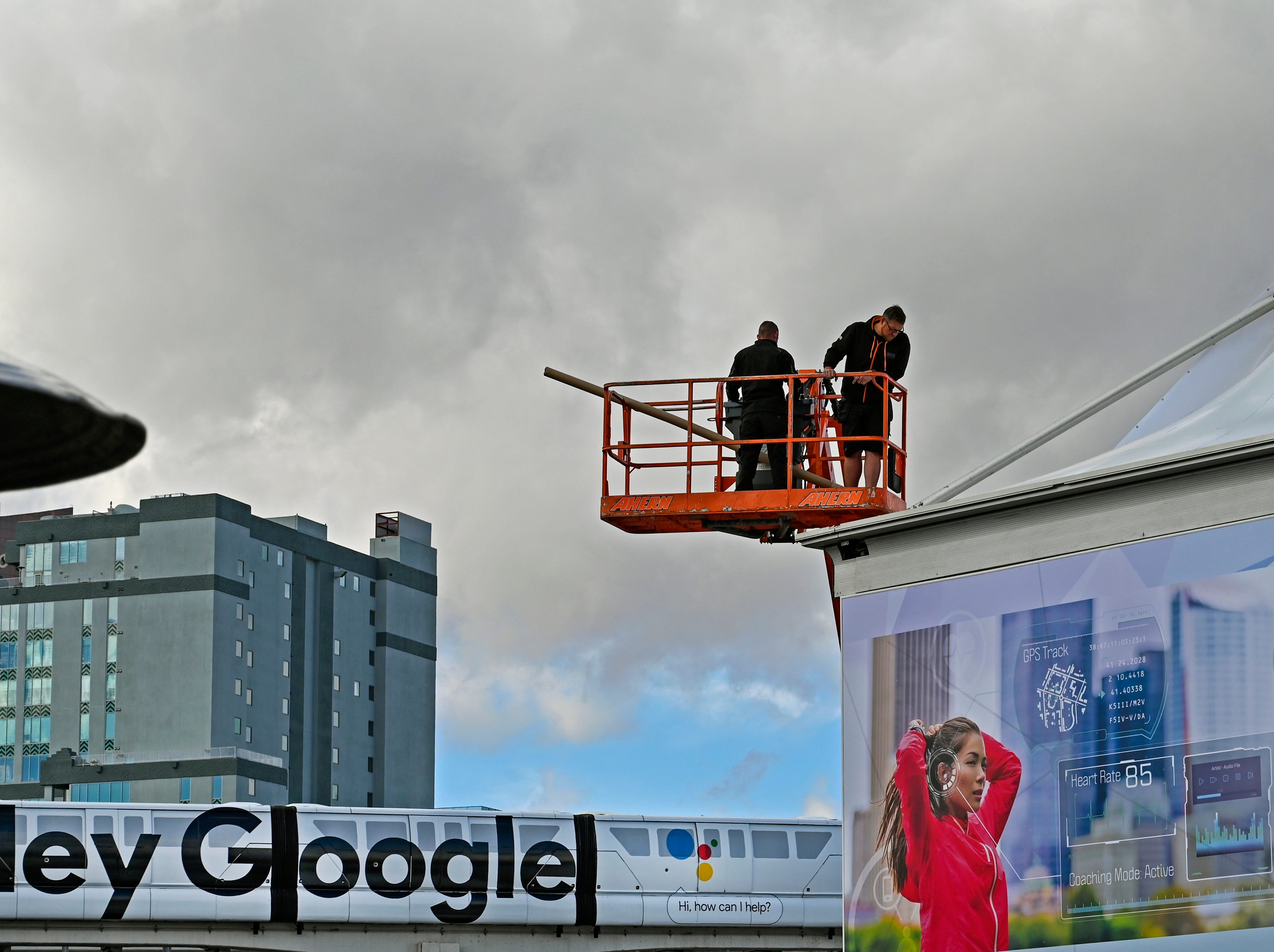 A work crew hangs banners on a large tent outside of the Las Vegas Convention Center as the monorail goes by in the background.