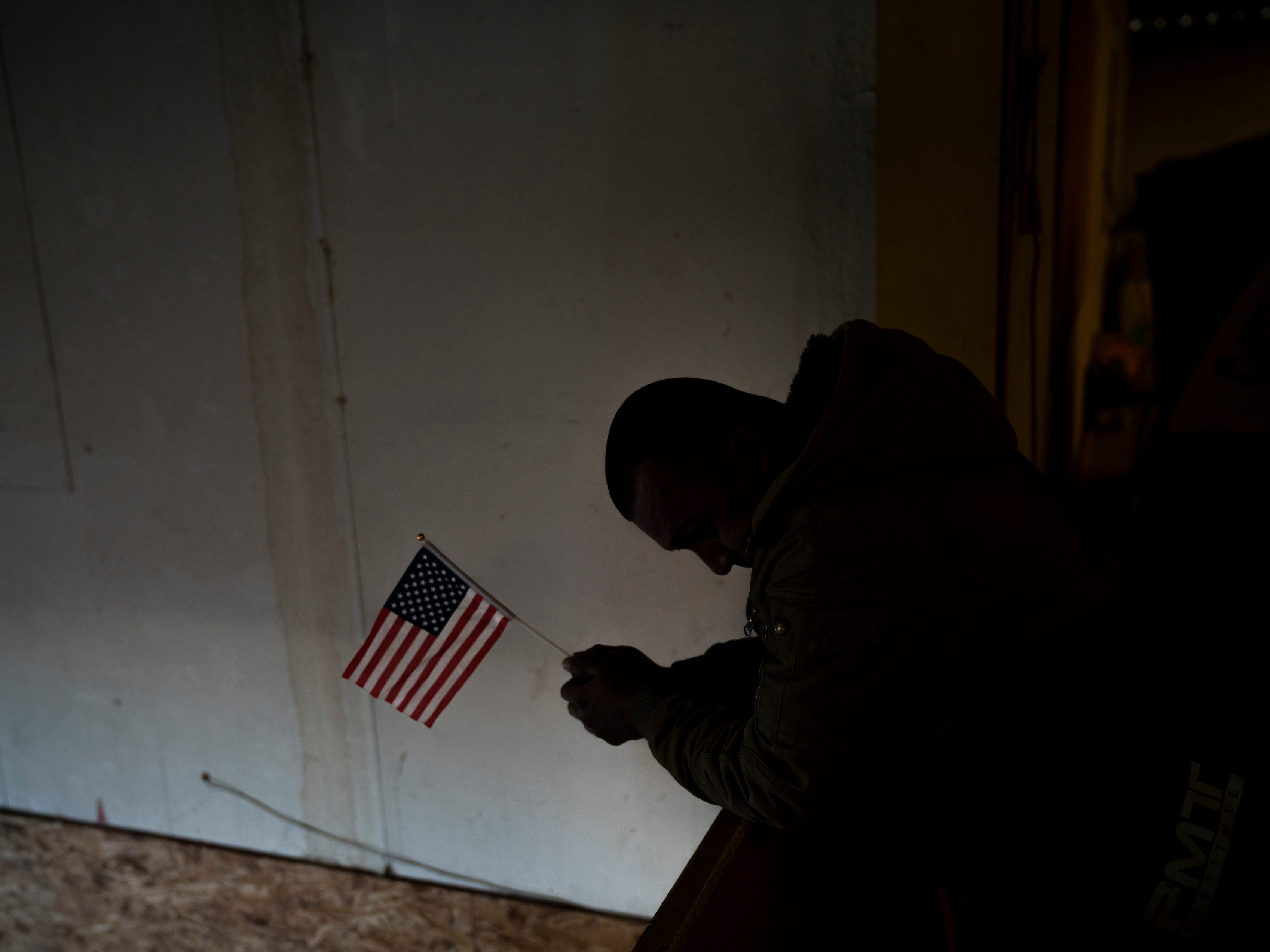 A migrant from Honduras holds a U.S. flag inside an empty warehouse used as a shelter set up for migrants in downtown Tijuana, before been relocated to other shelters in Tijuana, Mexico, Friday, Jan. 4, 2019.