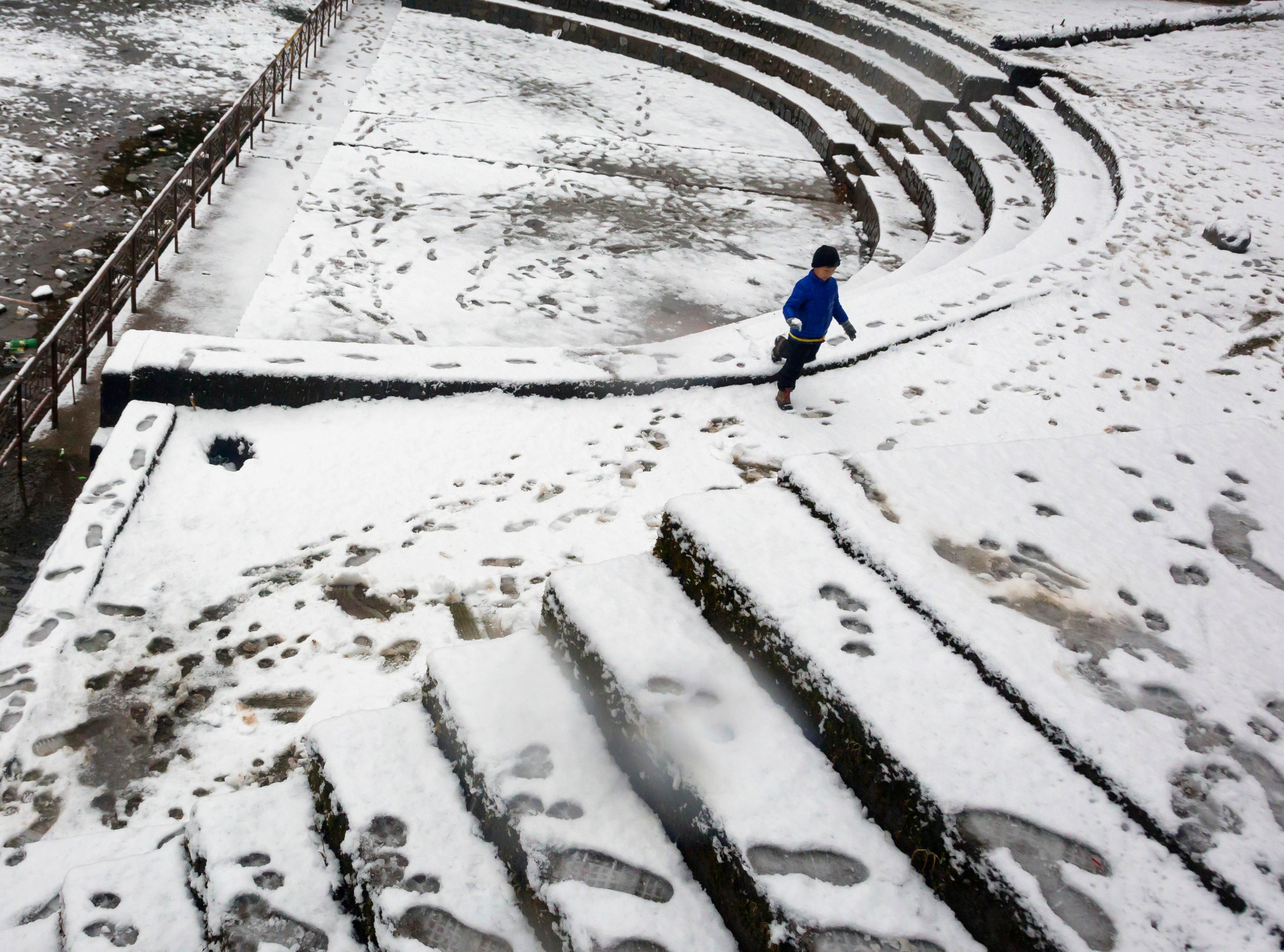 A young boy plays in snow in Dharmsala, India, Sunday, Jan. 6, 2019. The Himalayan region received season's first snowfall Sunday.