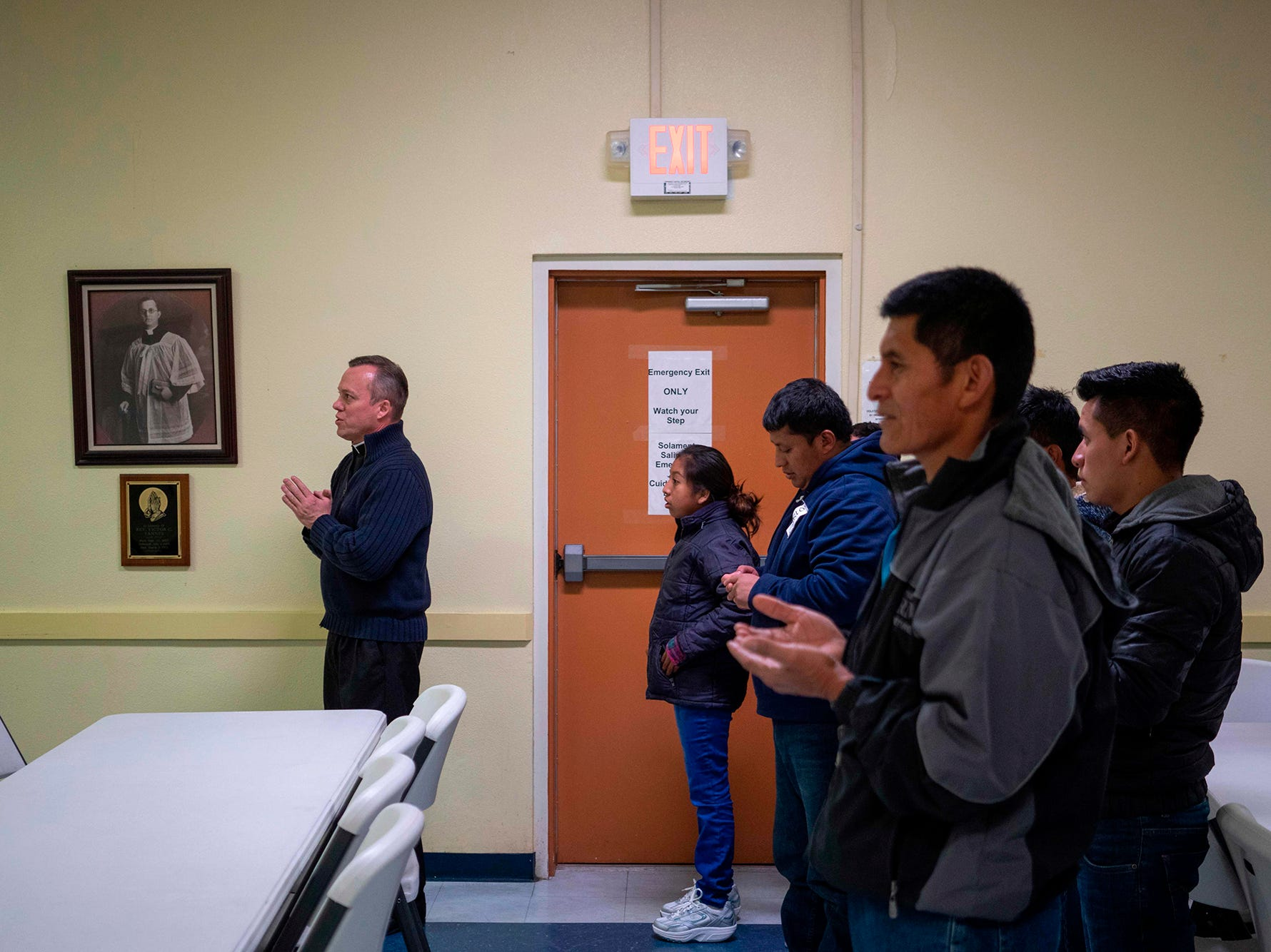 """Father Christopher Williams, left, says a blessing in the church hall of the Basilica of San Albino with a group of about 20 Central American migrants who were released by Immigration and Customs Enforcement that day in Mesilla, New Mexico on Jan. 2, 2019.  About 20 migrants were hosted by the church for a night before they would depart to their families in different parts of the United States. San Albino is taking part in a program called """"Project Oak Tree"""" which provides hospitality to migrants the day they are released by Immigration and Customs Enforcement. Without such shelters like this and those run by Annunciation house in El Paso, they would be left at a Greyhound Station in downtown El Paso, with no food, shelter or means of communication with their families."""