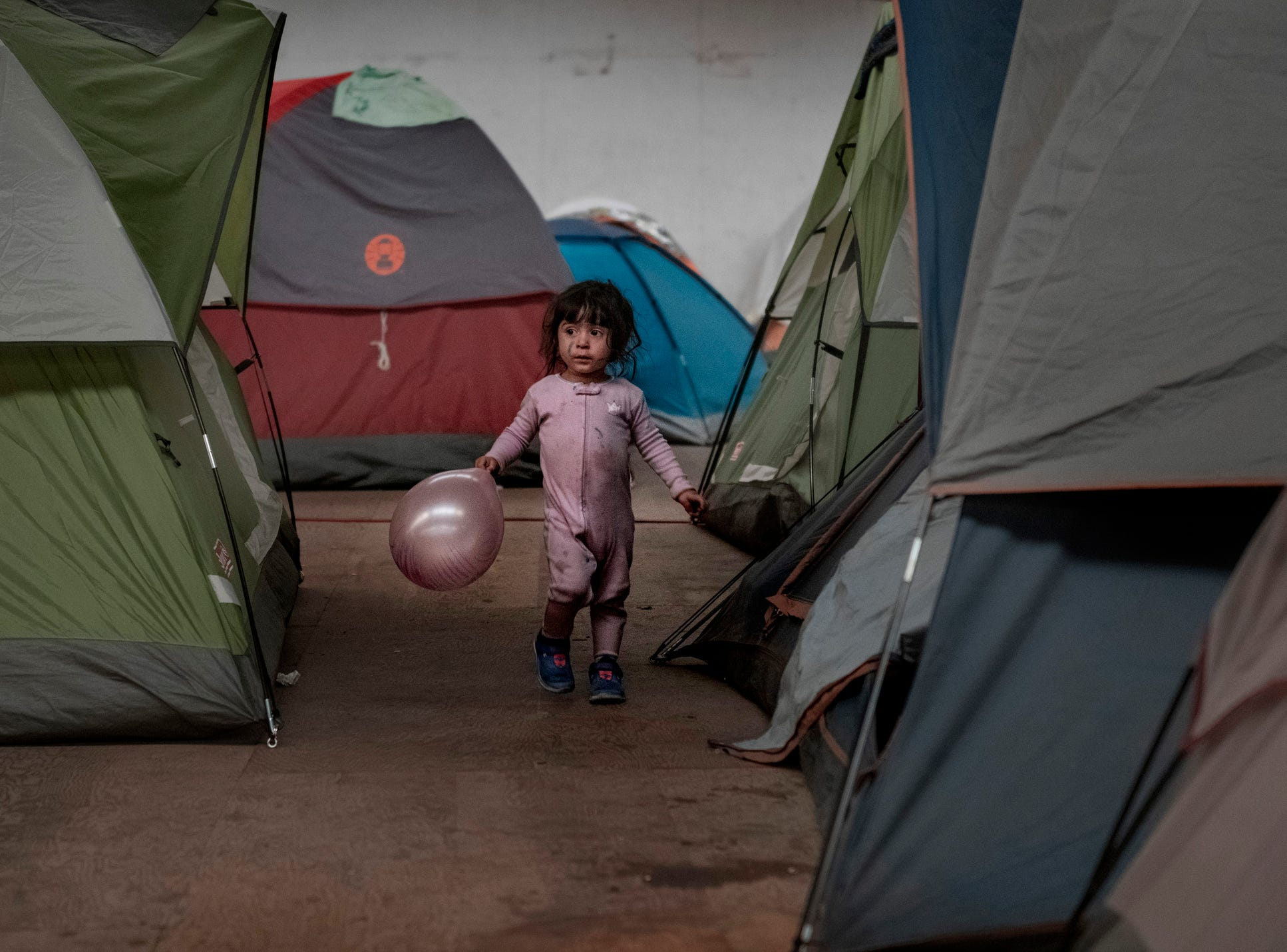 A girl holds a balloon as she walks among tents inside an empty warehouse used as a shelter set up for migrants in downtown Tijuana, Mexico, Wednesday, Jan. 2, 2019.