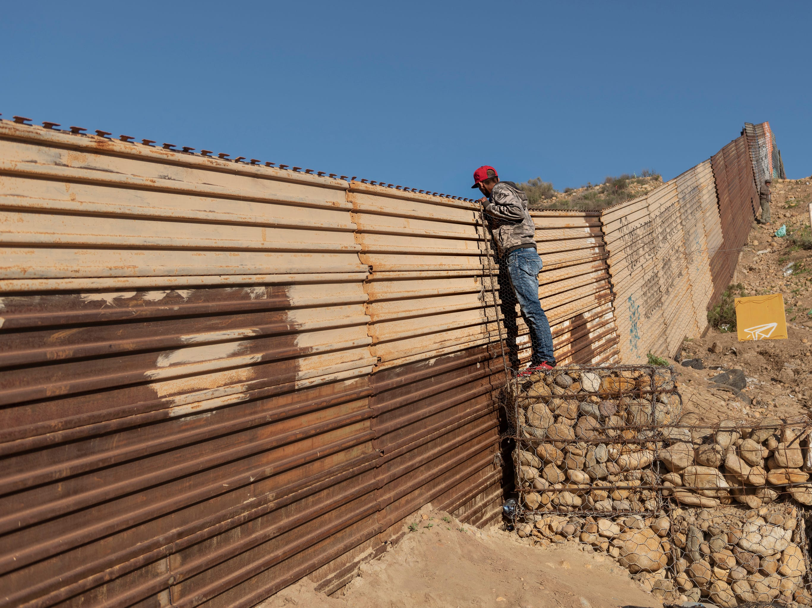 A migrant from Honduras looks from the border fence into the U.S. side to San Diego, Calif., from Tijuana, Mexico, Thursday, Jan. 3, 2019.