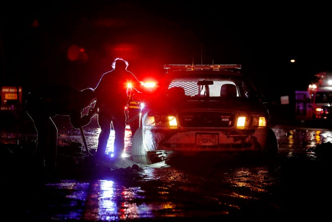 Sheriff's deputies work to free their patrol cruiser from mud covering a stretch of Pacific Coast Highway in Malibu, California, on Jan. 5, 2019.