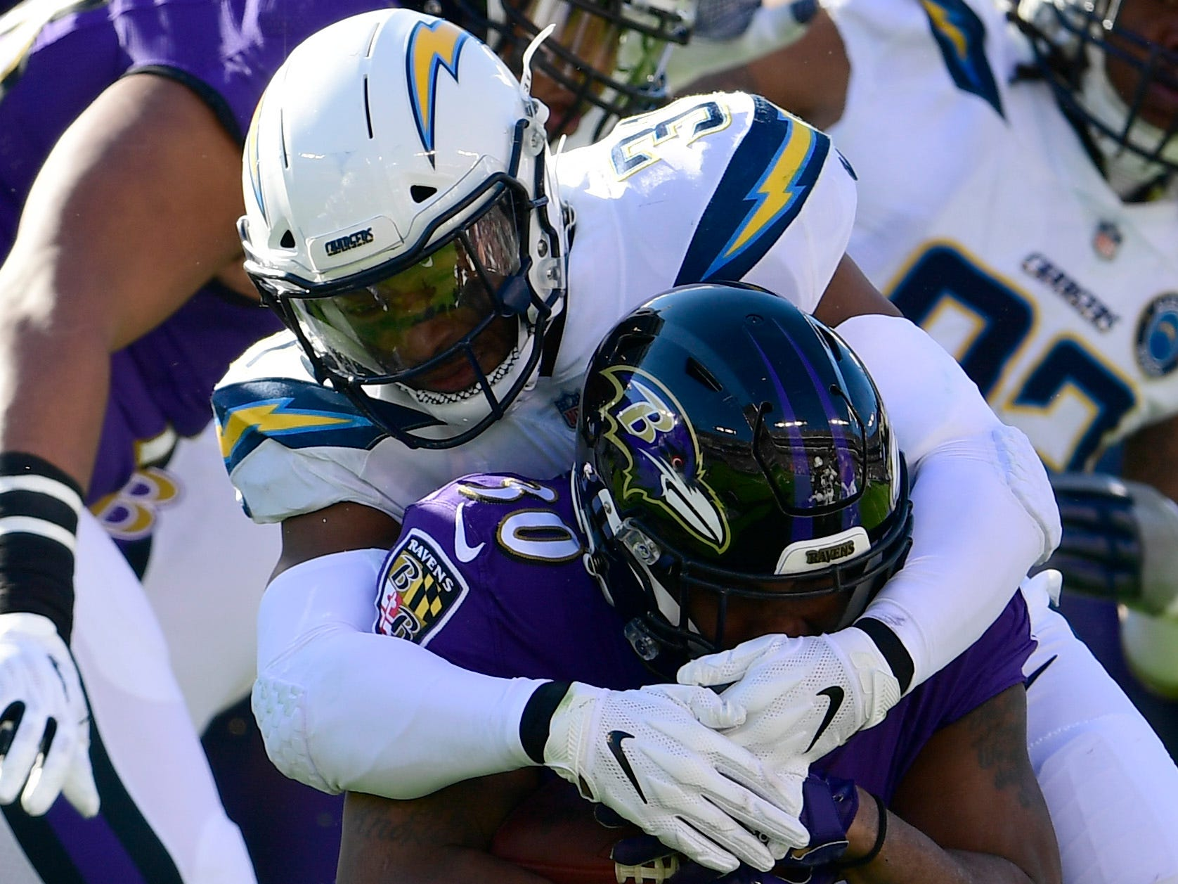 Jan 6, 2019; Baltimore, MD, USA; iLos Angeles Chargers safety Adrian Phillips (31) tackles Baltimore Ravens running back Kenneth Dixon (30) dung the first quarter n a AFC Wild Card playoff football game at M&T Bank Stadium. Mandatory Credit: Tommy Gilligan-USA TODAY Sports