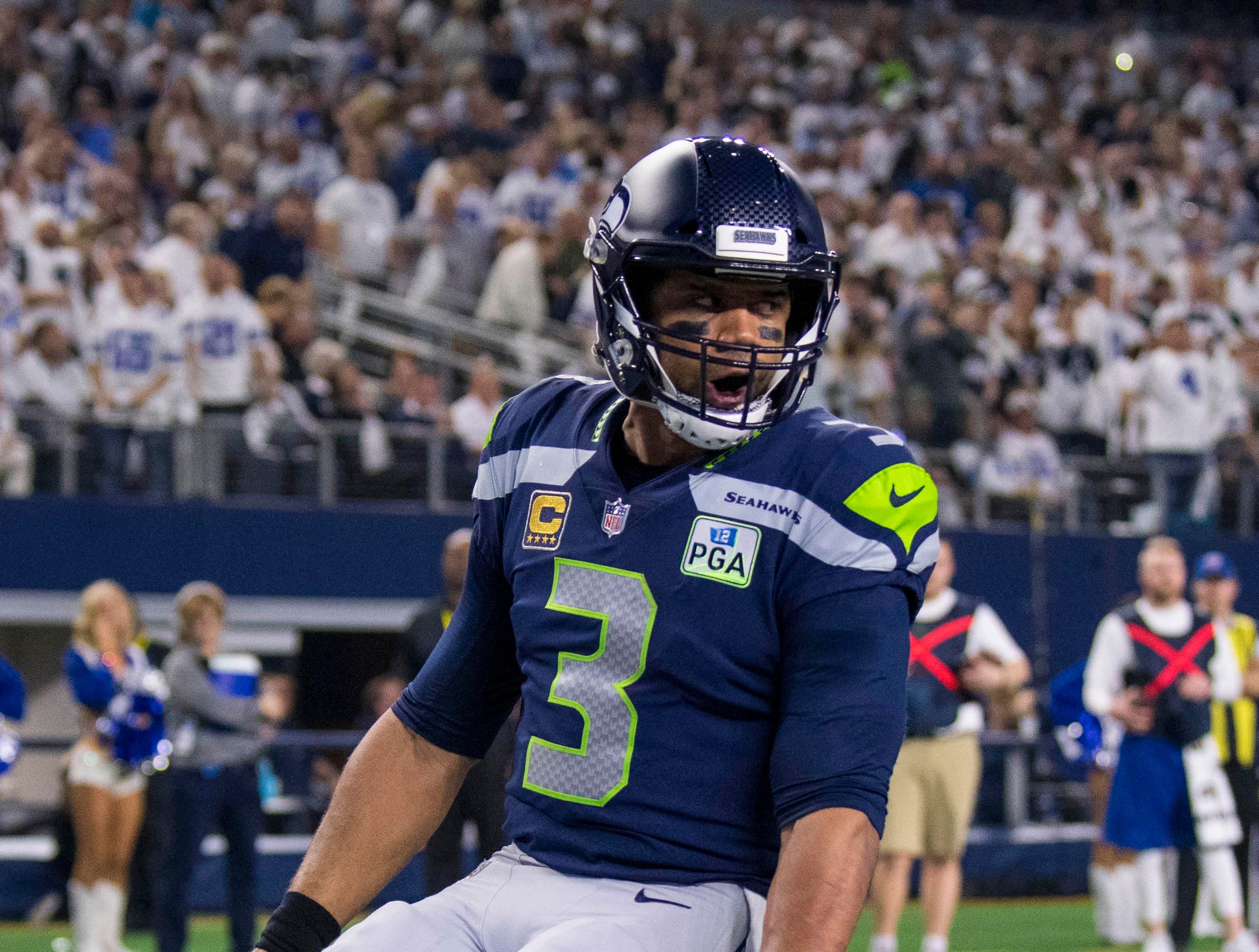 Seattle Seahawks quarterback Russell Wilson reacts after scoring a rushing touchdown against the Dallas Cowboys during the third quarter at AT&T Stadium.