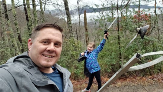 Marc Newland and his daughter Erica, 10, clean up trash in the Great Smoky Mountains National Park.
