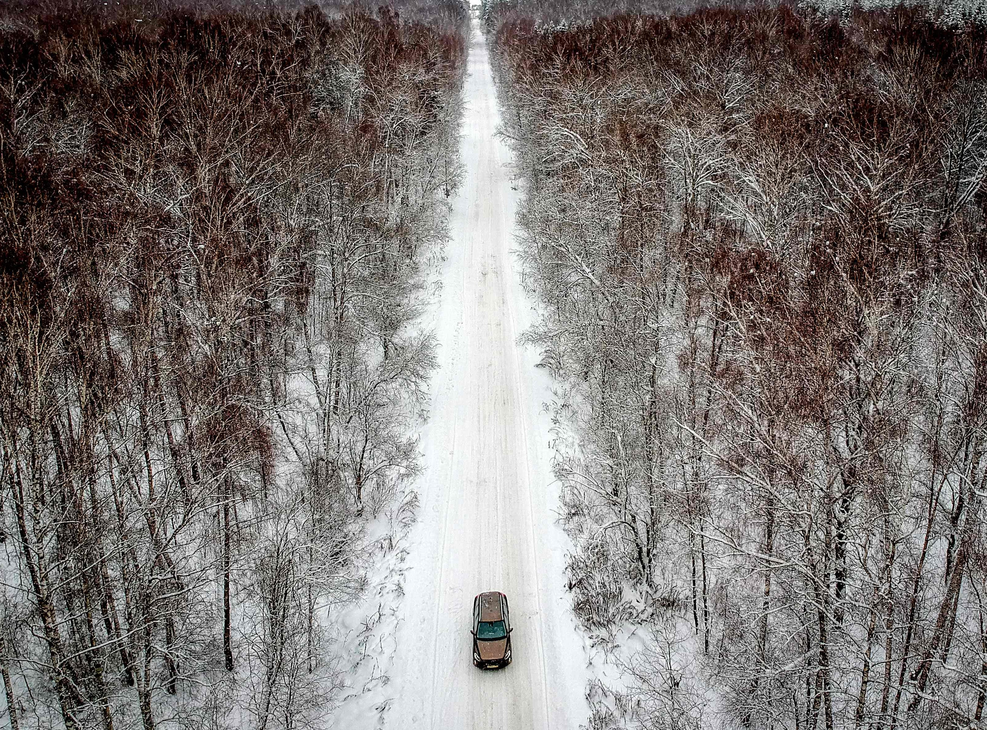 A car travels on a snow-covered forest road near the village of Meshcherskoye outside Moscow on Jan. 6, 2019.