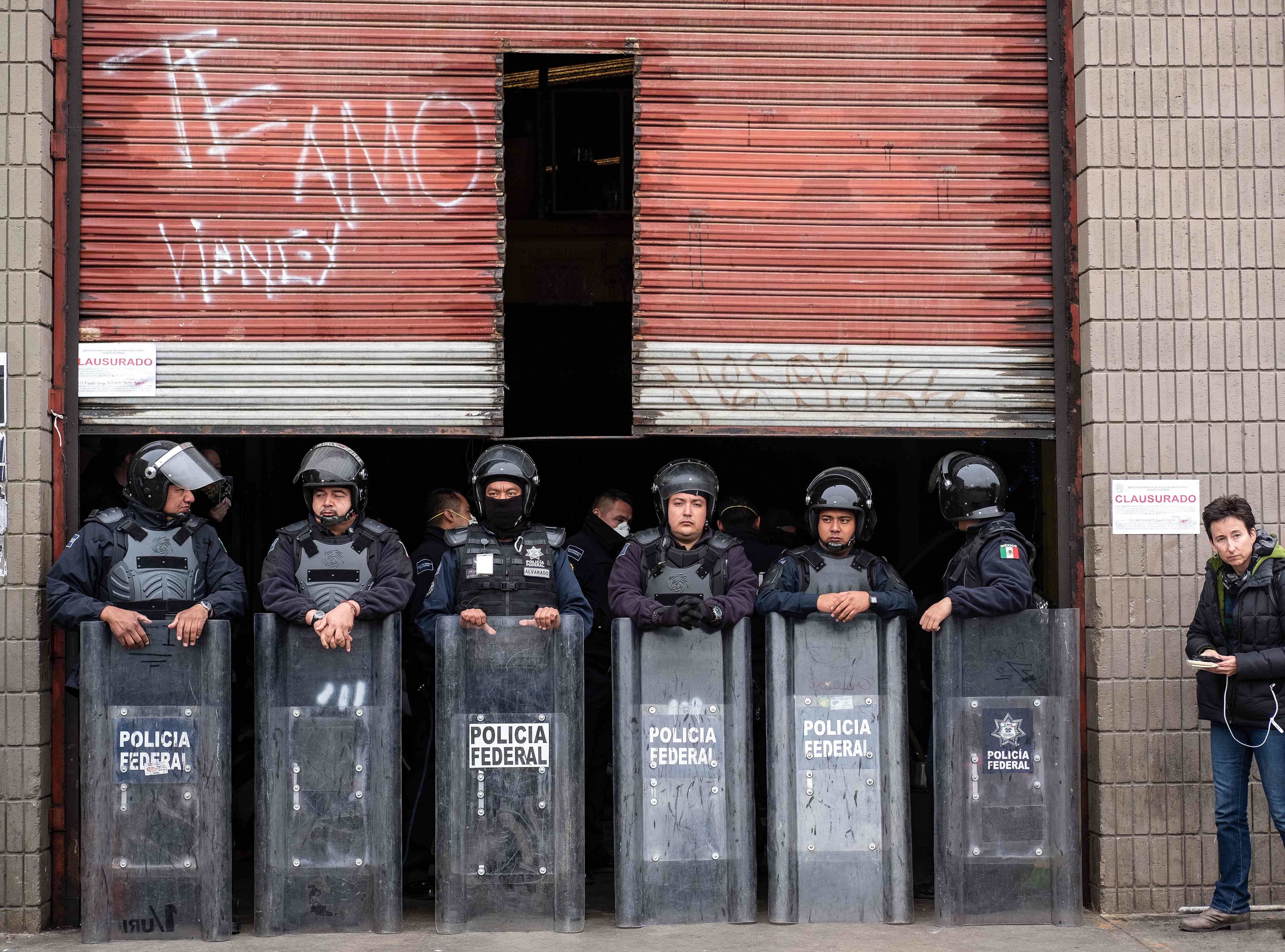 Federal Police officers stand guard at the entrance of a warehouse which was being used as a temporary shelter by Central American migrants wanting to reach the United States, in downtown Tijuana, Baja California State, Mexico, on Jan. 5, 2019. After a day long standoff with Federal Police, dozens of migrants who are to be relocated finally left the warehouse which authorities ordered to be closed due to sanitary conditions.