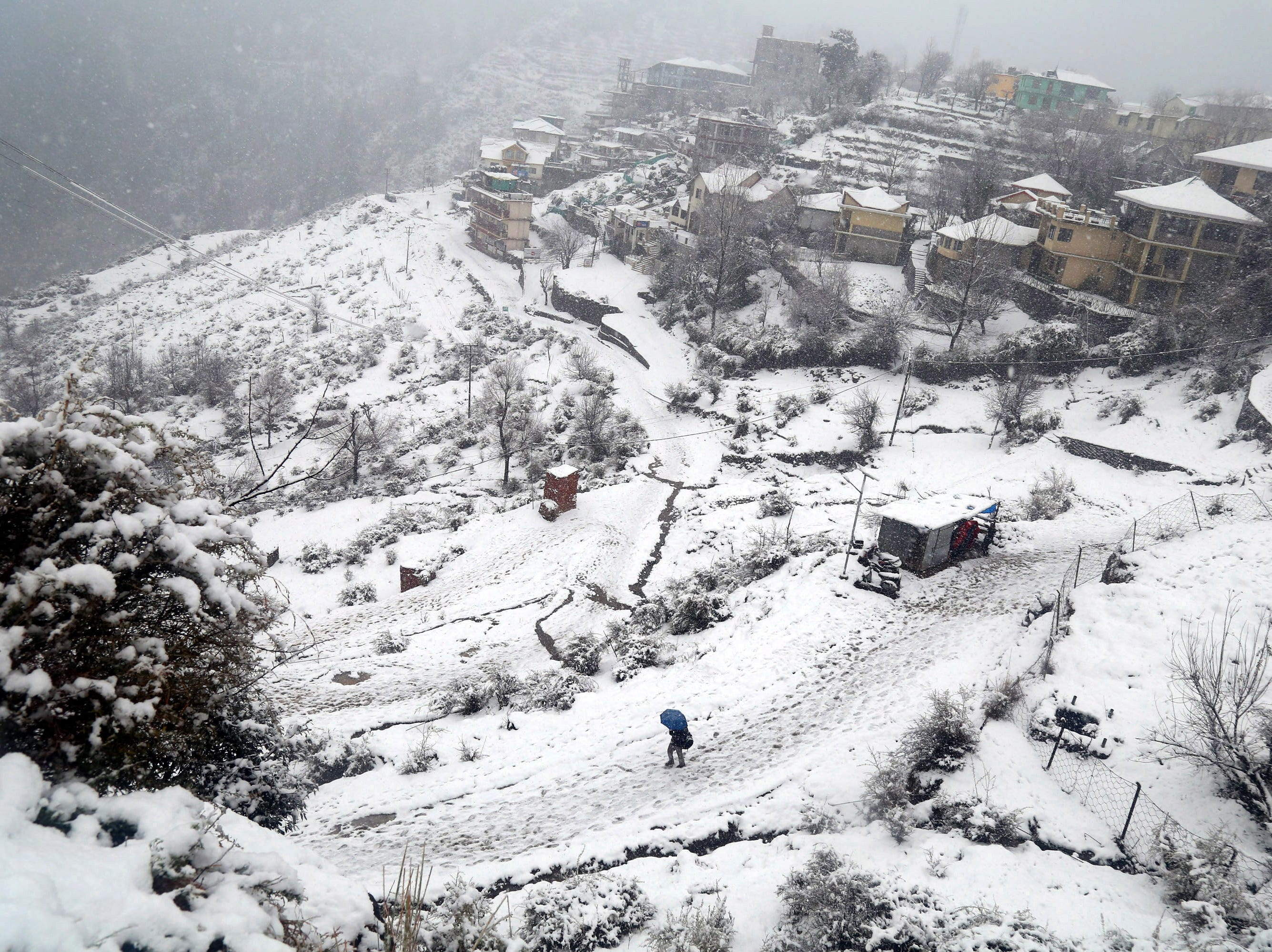 A person walks on snow after fresh snowfall at Naddi village near Dharamsala, India on Jan. 6, 2019. Intense cold wave conditions prevail in northern India as temperatures dipped at several places in the region with districts of Shimla, Kullu, Manali, Kinnaur, Chamba, and Pangi-Bharmaur of Himachal Pradesh receiving snowfall.