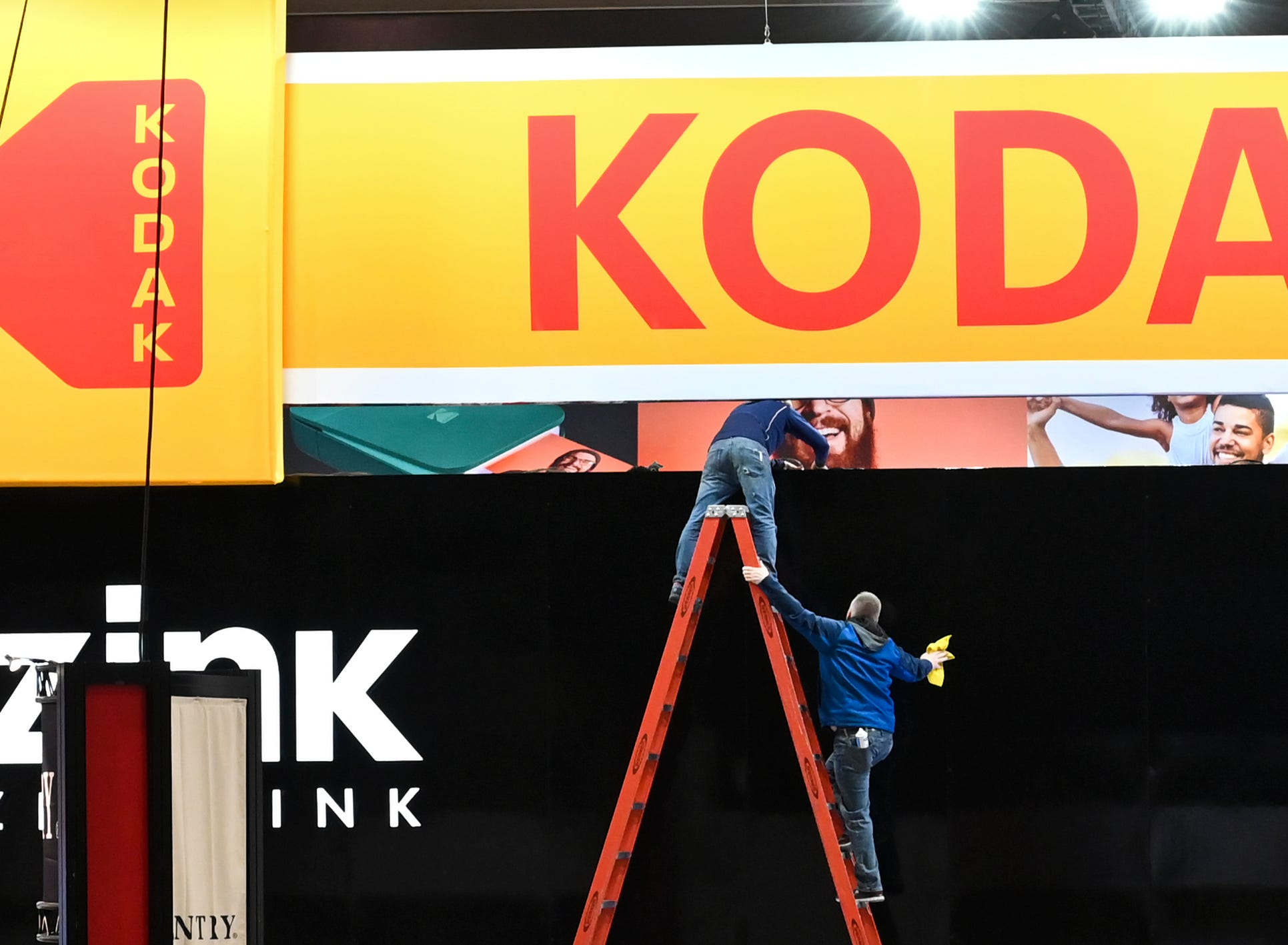 Workers clean up signage at the Kodak display in the Central Hall of the Las Vegas Convention Center.