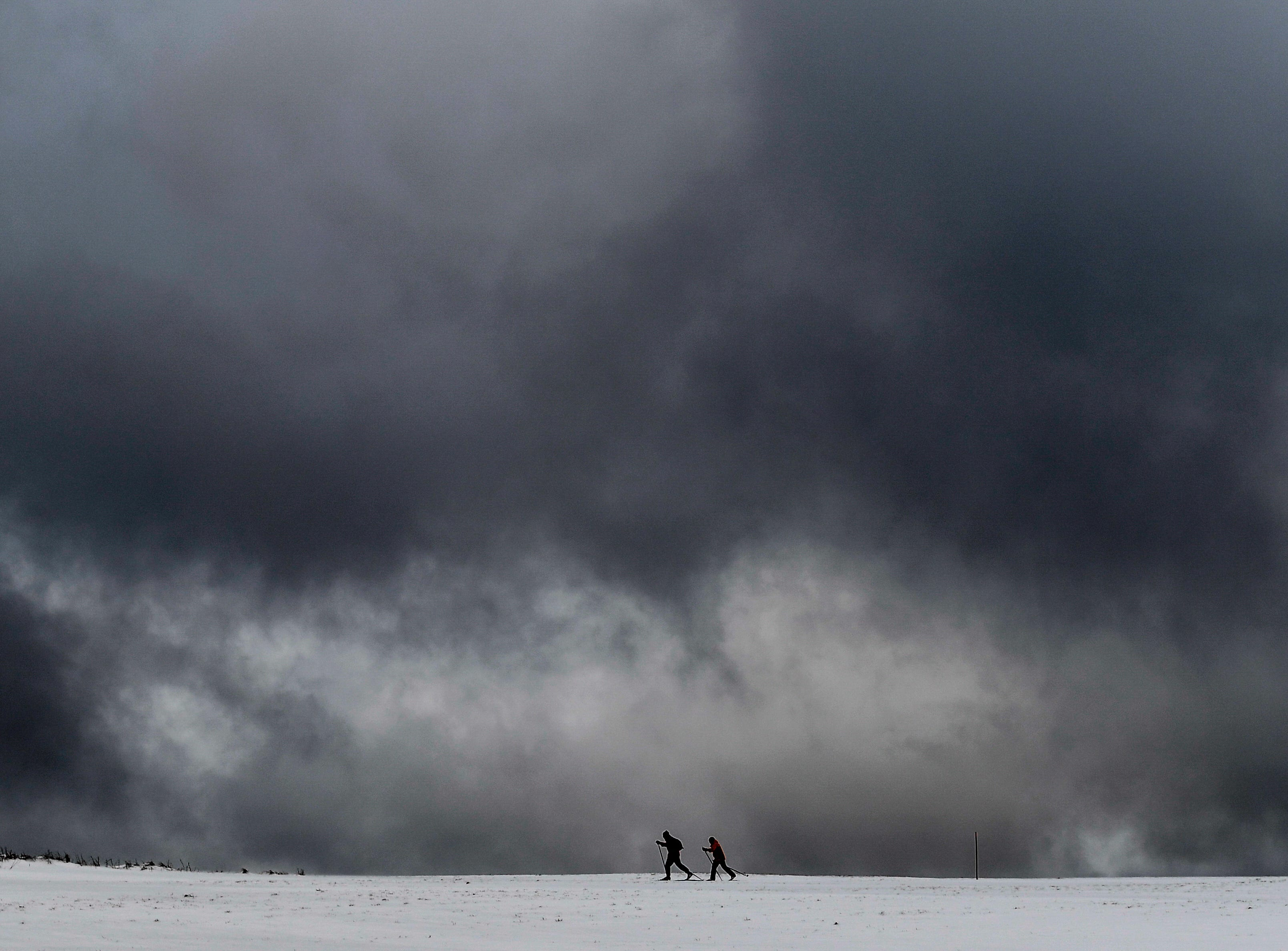 Cross country skiers move on their trip across a snow covered field of the Ore Mountains,  near Altenberg, Germany on Jan. 6, 2019.