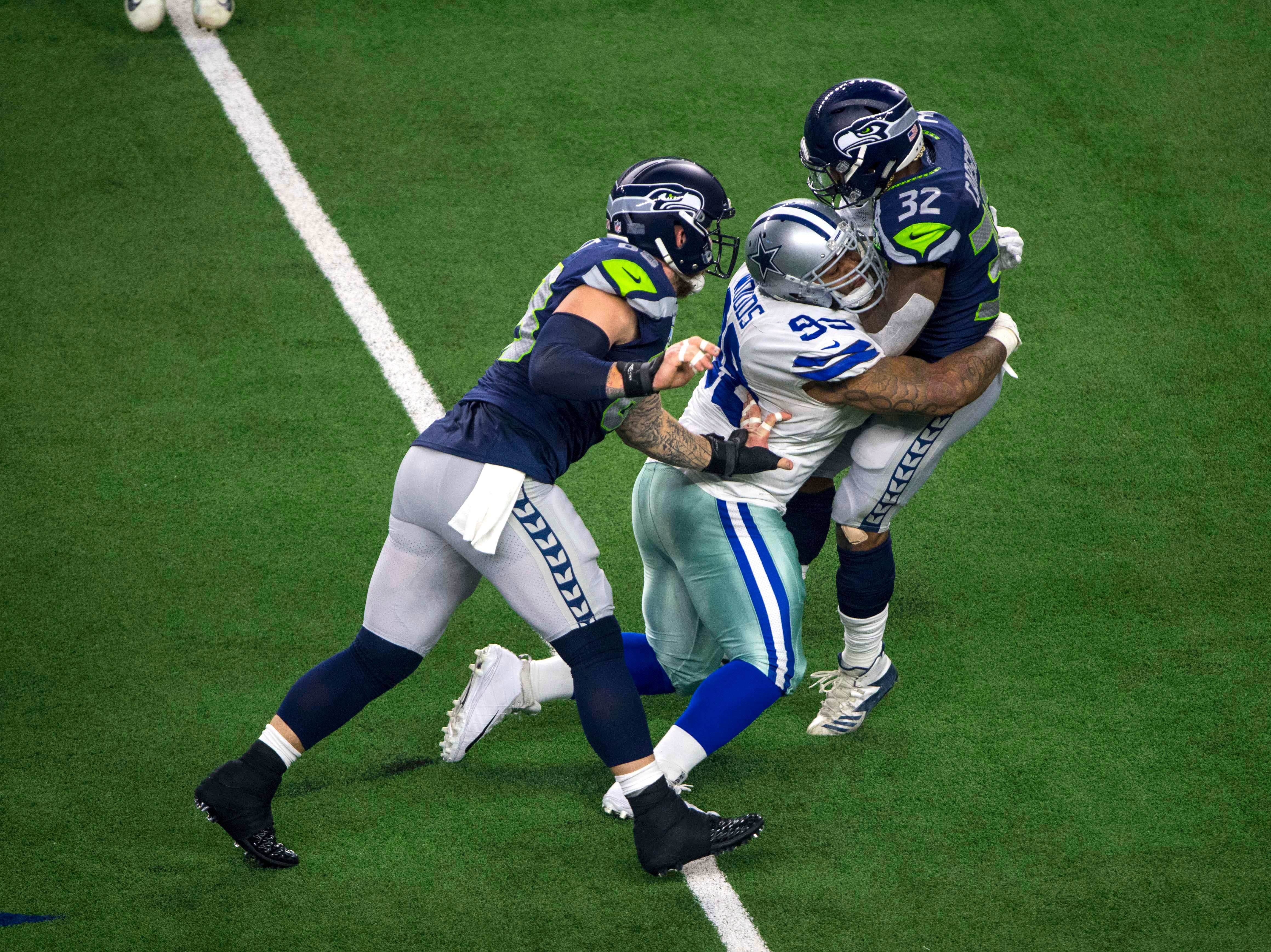 Seattle Seahawks running back Chris Carson (32) is tackled by Dallas Cowboys defensive tackle Antwaun Woods (99) during the first quarter at AT&T Stadium.