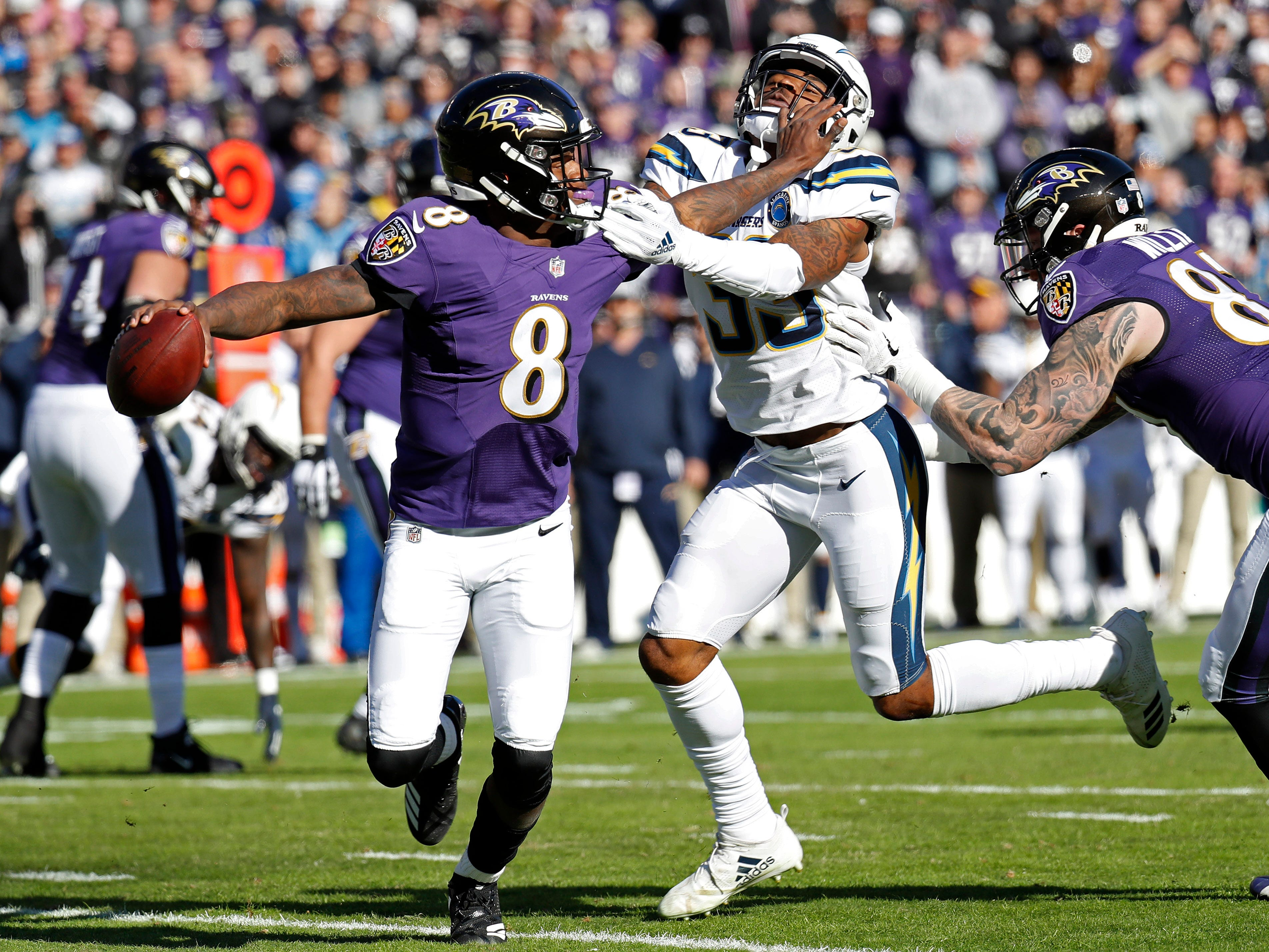 Baltimore Ravens quarterback Lamar Jackson (8) scrambles from Los Angeles Chargers free safety Derwin James (33) in the first quarter in a AFC Wild Card playoff football game at M&T Bank Stadium.