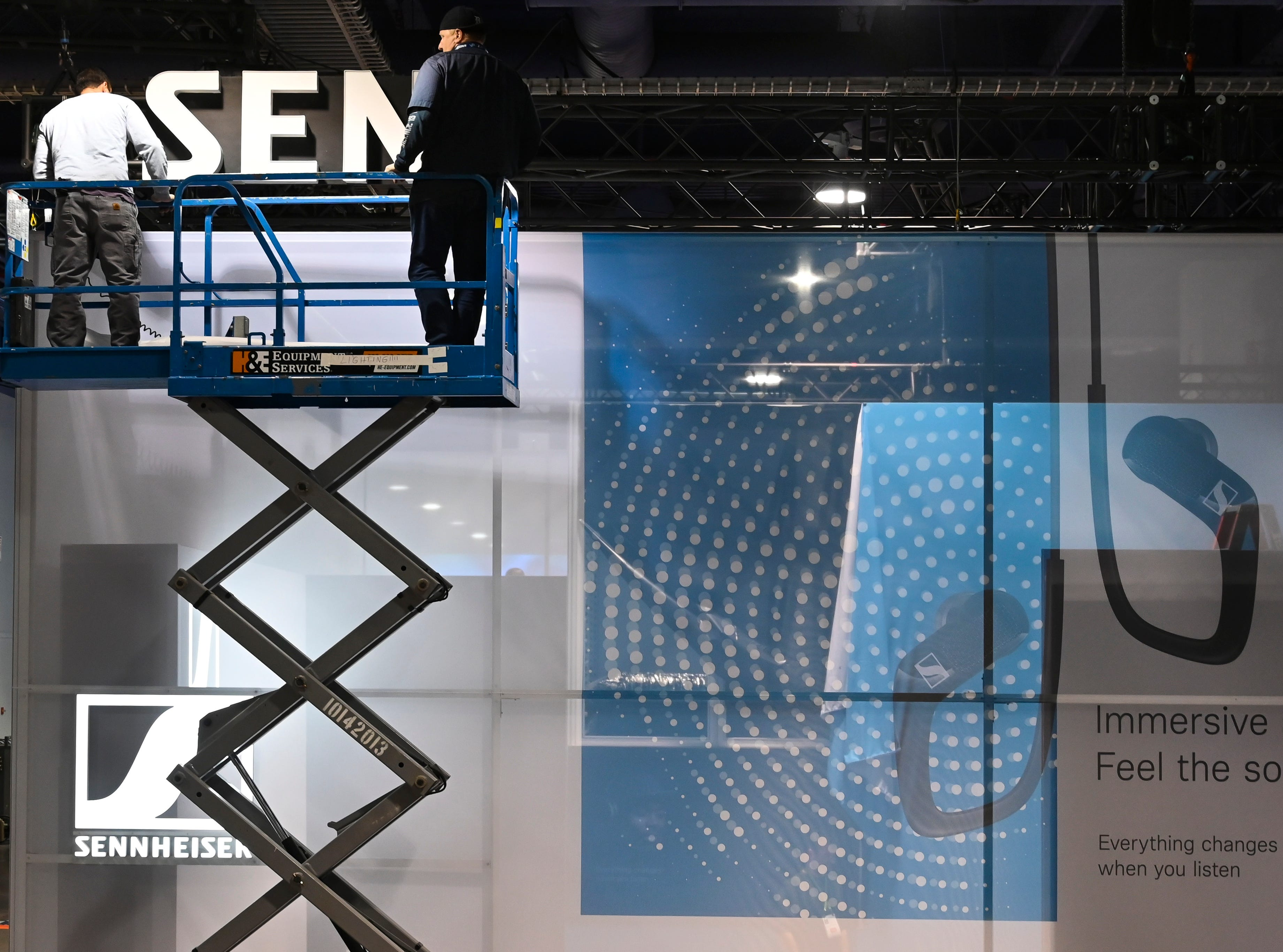 A work crew constructs the Sennheiser display in the South Hall of the Las Vegas Convention Center.
