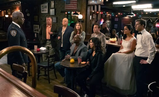"The cast of ""Brooklyn Nine-Nine"" listens to Capt. Ray Holt (Andre Braugher) in the Season 6 premiere, which picks up after May's season-finale wedding of Jake and Amy."