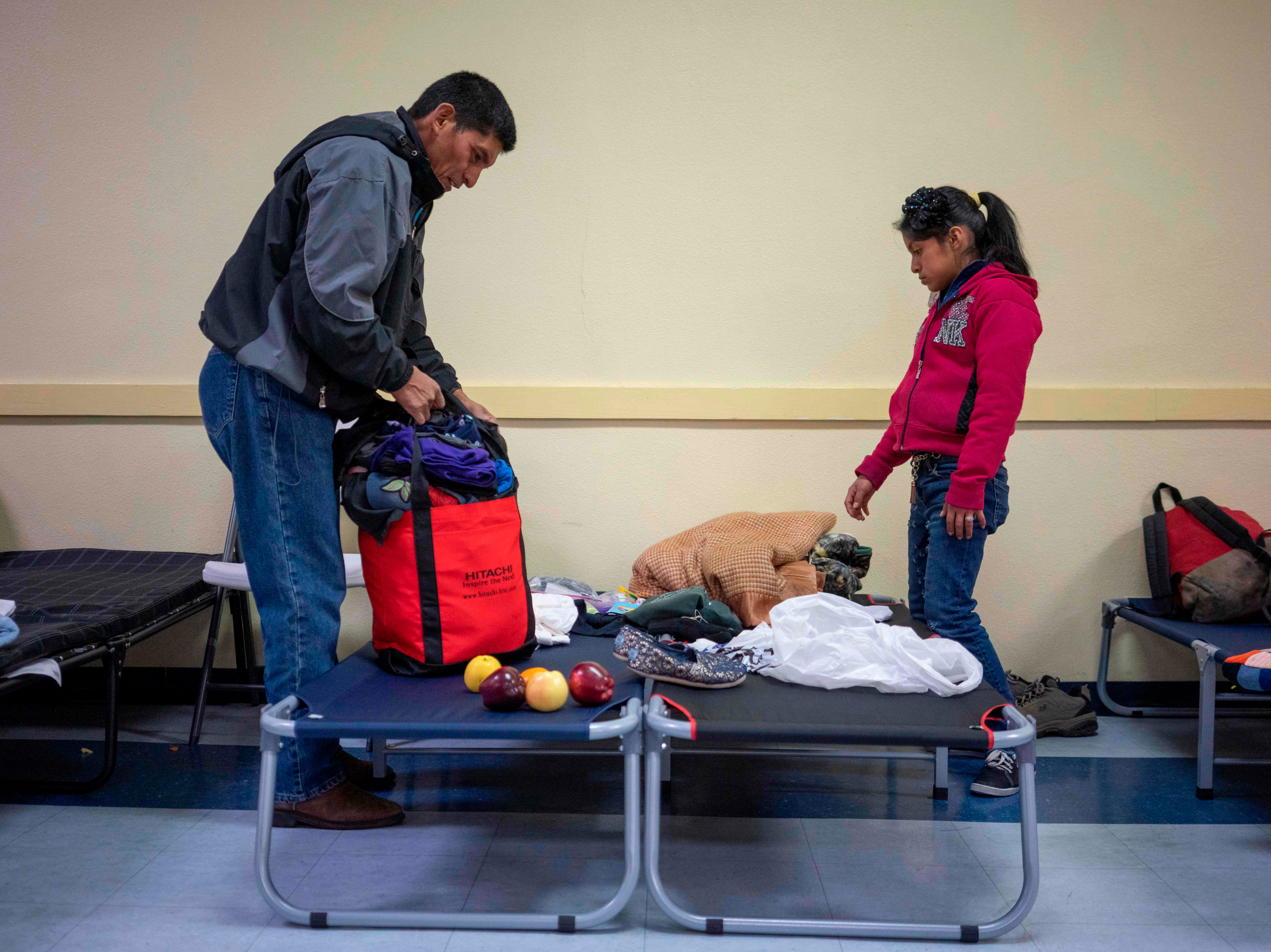 Ovidio Lopez Tum, left, 53, and his daughter Ingrid Maribel, 12, pack up their belongings for their trip the following day, at the church hall of the Basilica of San Albino in Mesilla, New Mexico on Jan. 2, 2019.