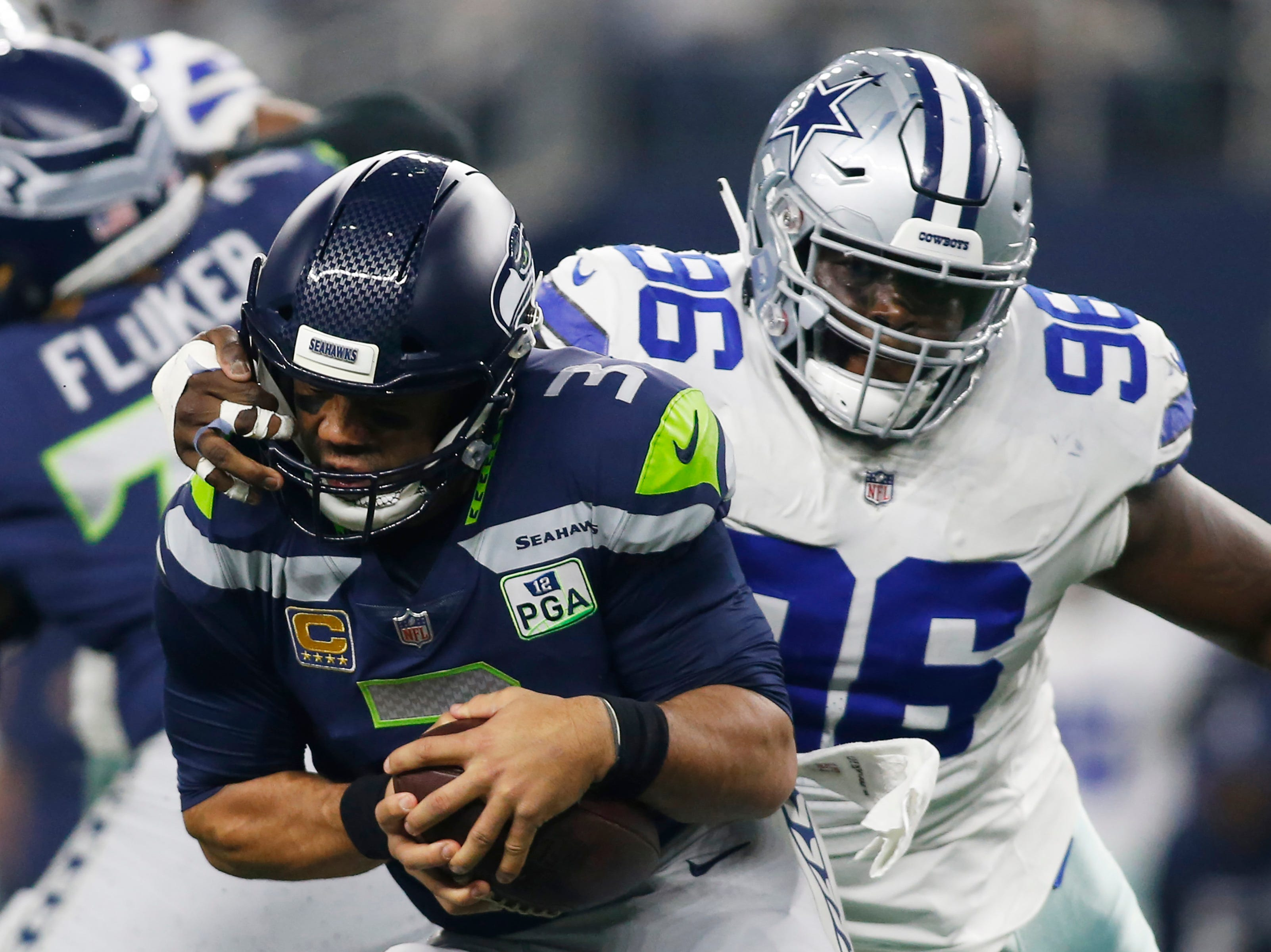 Seattle Seahawks quarterback Russell Wilson (3) is sacked by Dallas Cowboys defensive tackle Maliek Collins (96) in the first quarter at AT&T Stadium.